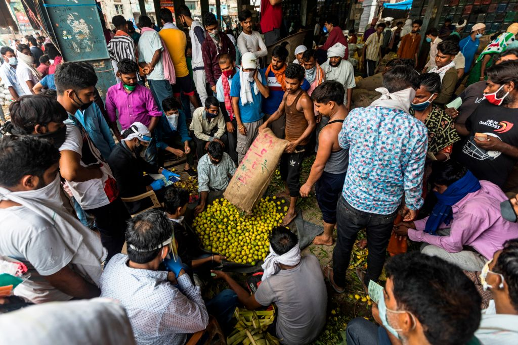 Buyers gather as vendors auction sacks of lemons at Azadpur wholesale vegetable market after the government eased a nationwide lockdown imposed as a preventive measure against the spread of the COVID-19 coronavirus, in New Delhi on June 26, 2020. (Photo by XAVIER GALIANA/AFP via Getty Images)
