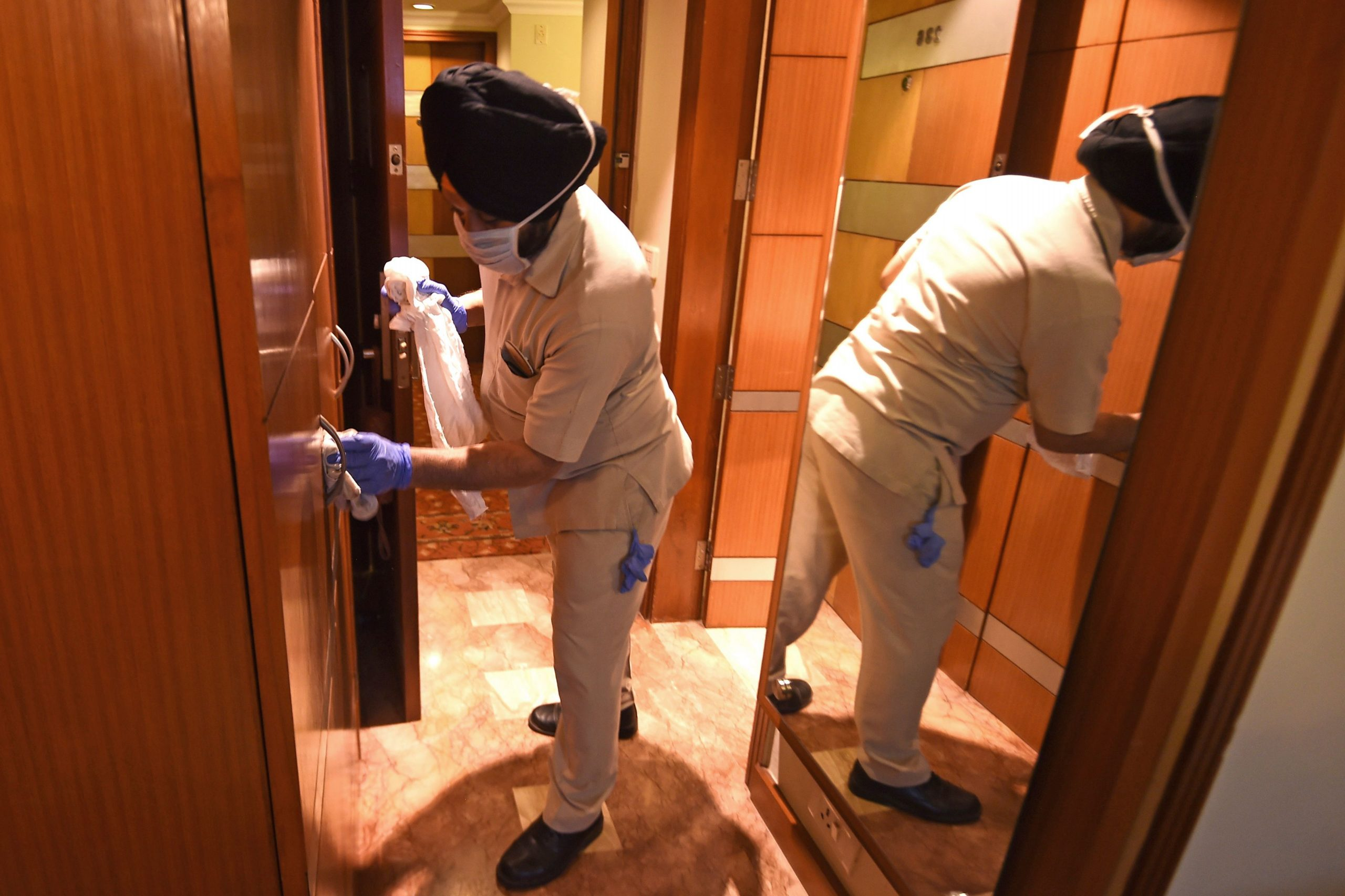 A housekeeping employee of the Suryaa hotel cleans a room in New Delhi. - Staff at the luxury Suryaa hotel used to welcome guests in bright saris. Now they must don medical suits and handle gurneys as New Delhi desperately prepares for a predicted surge in coronavirus cases in the coming weeks. (Photo by Money SHARMA / AFP) /