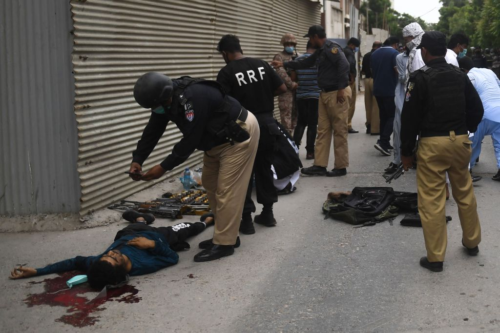 Police collect evidence next to a body of an alleged gunman outside the Pakistan Stock Exchange building in Karachi on June 29, 2020. - A group of gunmen attacked the Pakistan Stock Exchange in Karachi June 29, police said, with four of the attackers killed. (Photo by ASIF HASSAN/AFP via Getty Images)