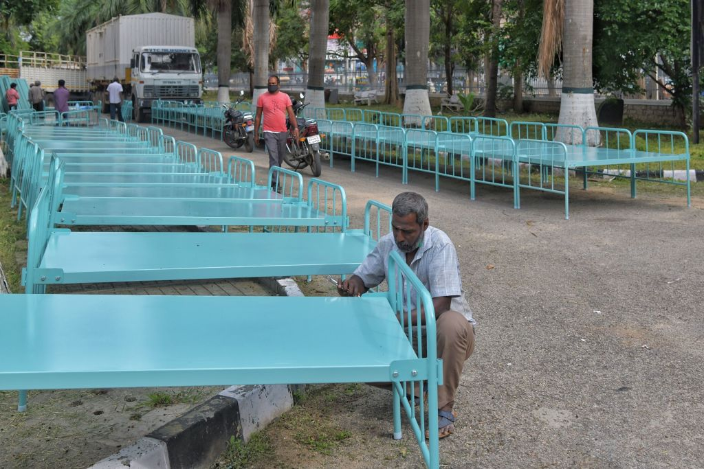Workers assemble metal cots outside the Koramangala indoor stadium, which is being converted into a temporary COVID-19 coronavirus care centre with over 250 beds, in an attempt to contain the spread of COVID-19 coronavirus, in Bangalore on June 29, 2020. (Photo by MANJUNATH KIRAN/AFP via Getty Images)