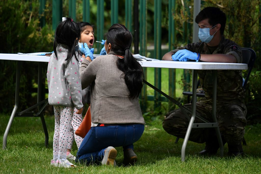 A family member administers a self-test to a child at a station set up for the testing for the novel coronavirus, in Spinney Hill Park, Leicester, on June 30, 2020. (Photo: JUSTIN TALLIS/AFP via Getty Images)