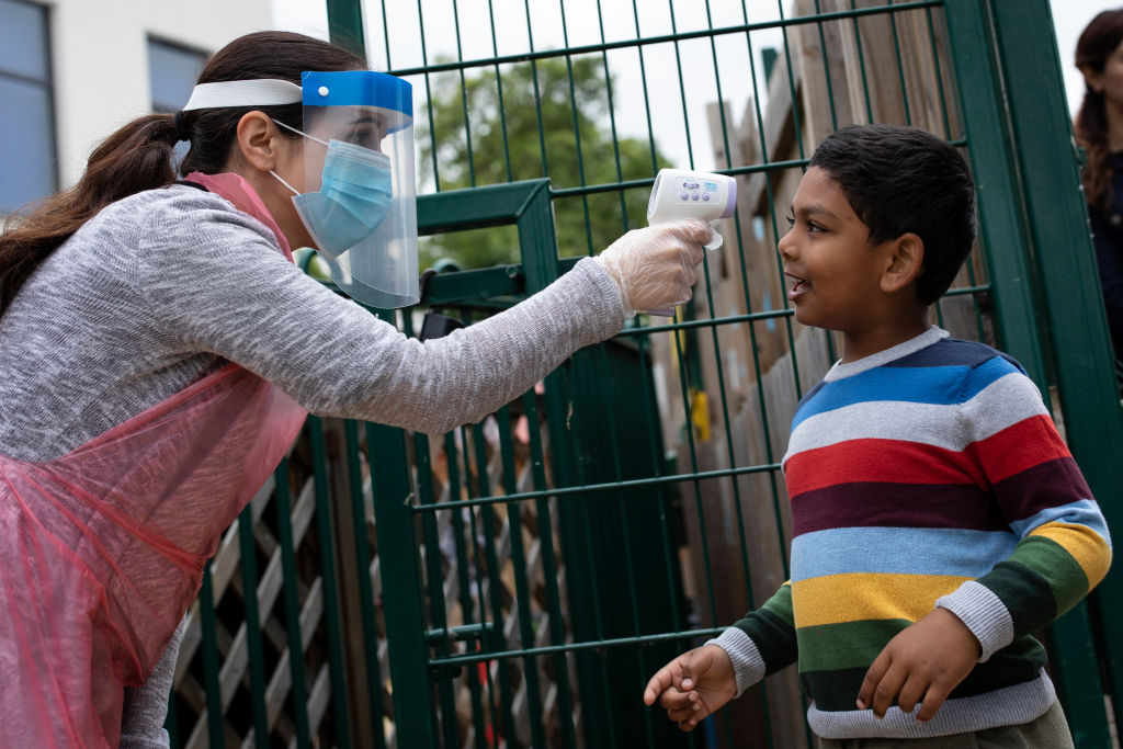 A staff member checks a child's temperature at the Harris Academy's Shortland's school on June 04, 2020 in London. (Photo: Dan Kitwood/Getty Images)