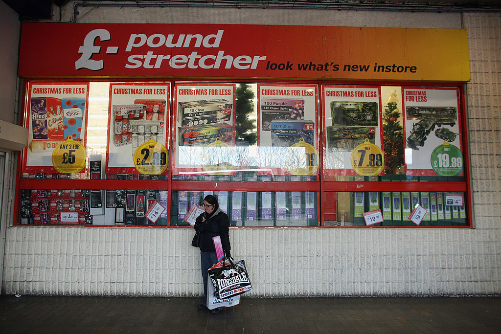 FILE PHOTO: A woman waits outside a branch of Poundstretcher near Lewisham high street in London, England.  (Photo by Oli Scarff/Getty Images)