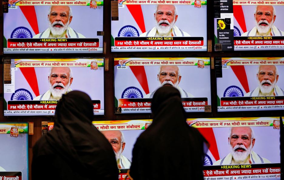 Women watch Indian Prime Minister Narendra Modi address the nation amid the spread of the coronavirus disease (COVID-19), on TV screens inside a showroom in Ahmedabad, India, June 30, 2020. REUTERS/Amit Dave