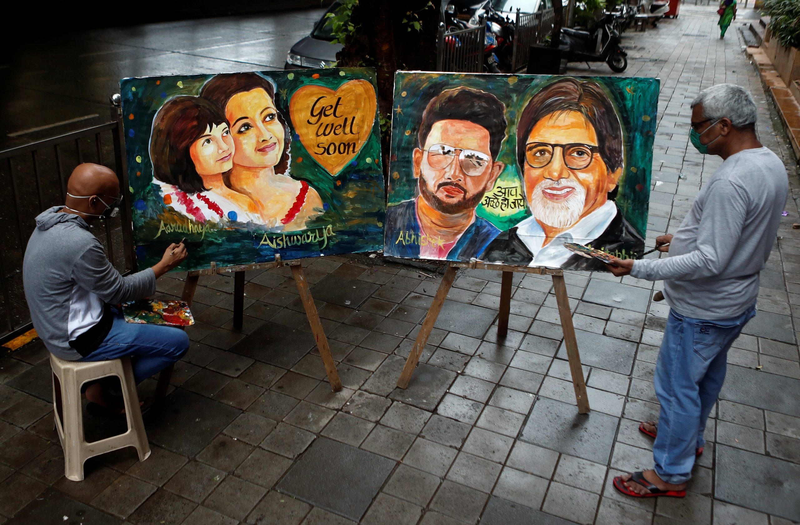 Artists create paintings depicting Bollywood actor Amitabh Bachchan, his son Abhishek Bachchan, his daughter-in-law Aishwarya Rai Bachchan and his granddaughter Aaradhya, after they tested positive for the coronavirus disease (COVID-19), in Mumbai, India, July 13, 2020. REUTERS/Francis Mascarenhas NO RESALES. NO ARCHIVES