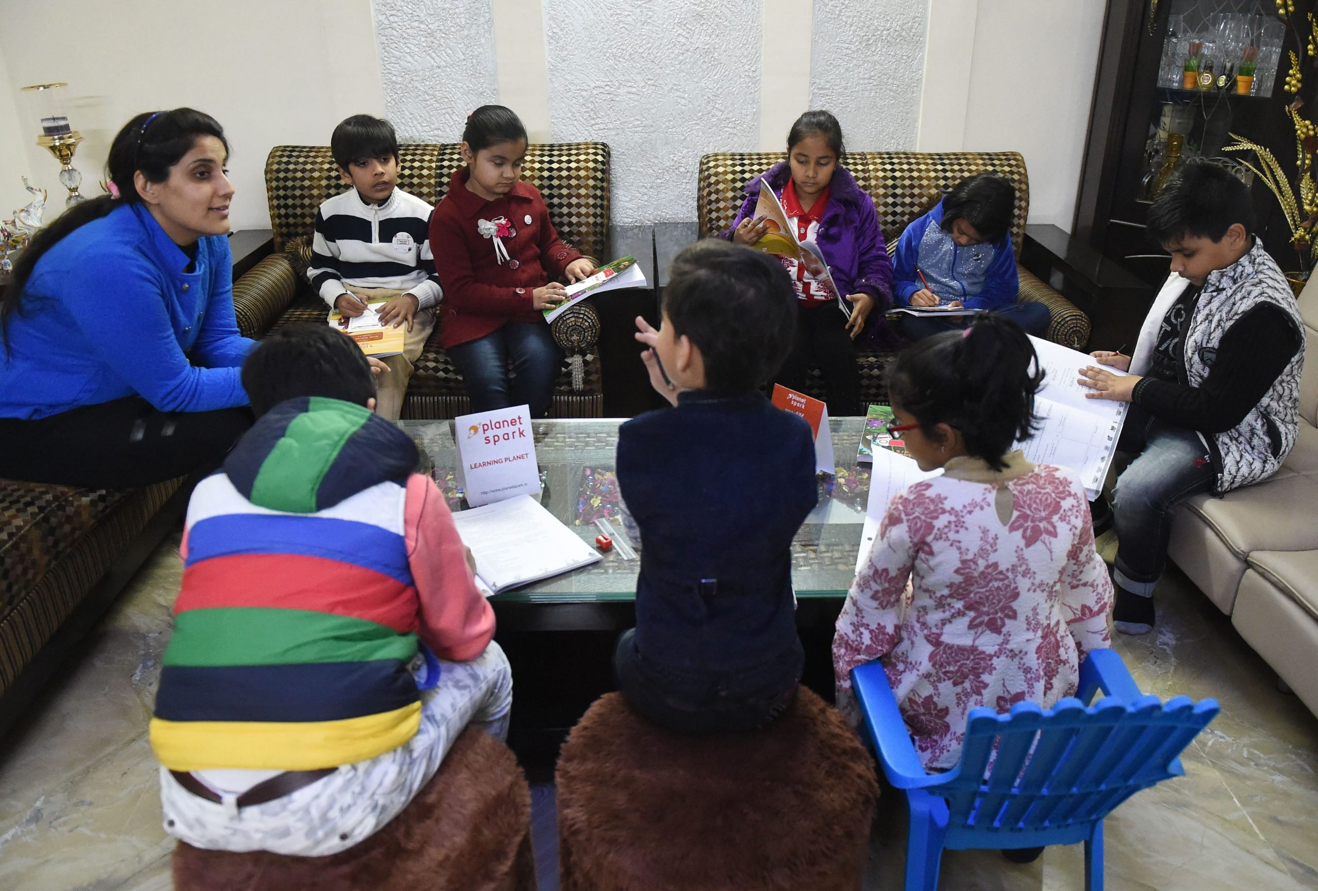 """In this photograph taken on February 13, 2019, Ruchi Taneja (L) teaches a group of Indian children studying with an app created by Planet Sparks that uses """"gamified"""" teaching methods at a tuition centre in New Delhi. - From a multi-billion-dollar education startup to wired-up mannequins, technology is helping to revolutionise the way Indian schoolchildren are learning -- provided their parents can afford it. (Photo by Money SHARMA / AFP) / To go with 'INDIA-ECONOMY-EDUCATION-TECHNOLOGY-AMAZON-BYJU',FOCUS by Vishal MANVE        (Photo credit should read MONEY SHARMA/AFP via Getty Images)"""