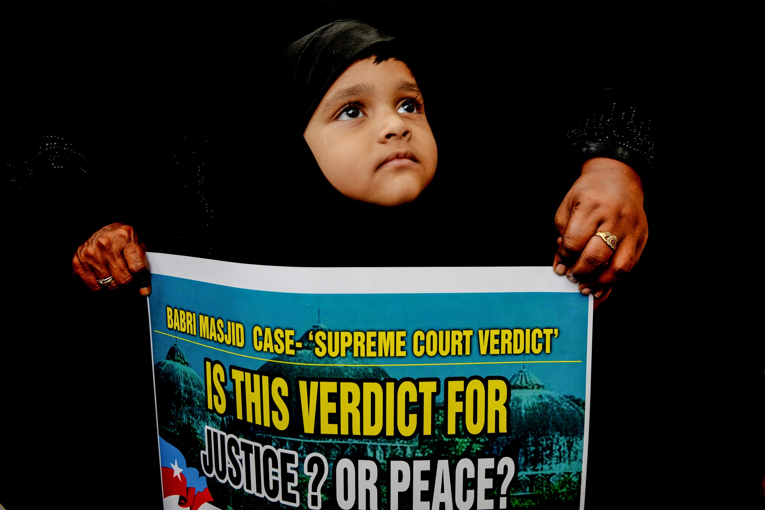 A muslim girl looks on as Muslims and members of Tamil ethnic group hold placards during a demonstration against the Supreme Court verdict awarded to Hindus on a disputed religious site of Ayodhya in Chennai on November 21, 2019. (Photo by ARUN SANKAR / AFP) Getty Images)