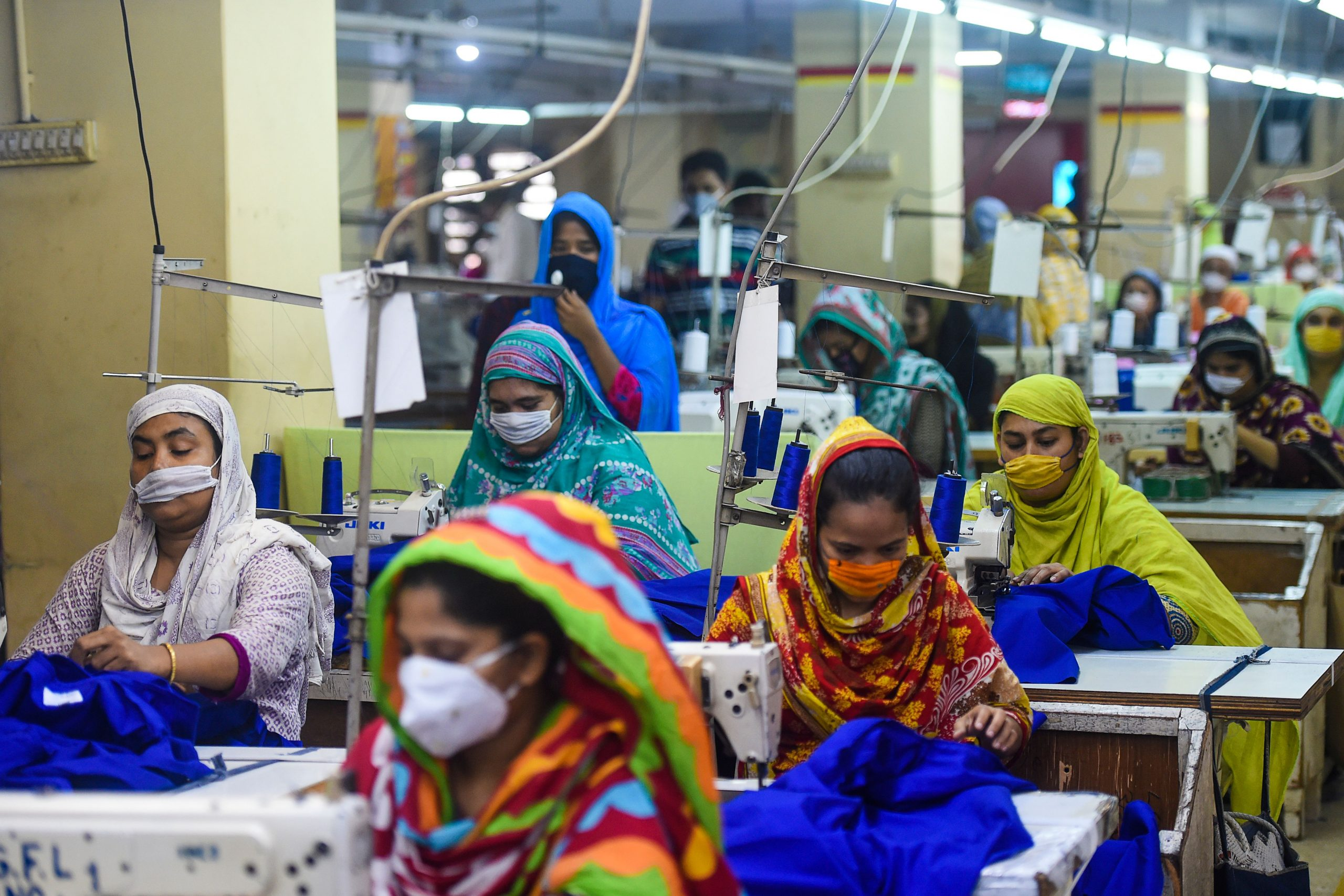 Labourers wearing facemasks work in a garment factory during a government-imposed lockdown as a preventive measure against the spread of the COVID-19 coronavirus in Dhaka on May 2, 2020. (Photo by MUNIR UZ ZAMAN / AFP) (Photo by MUNIR UZ ZAMAN/AFP via Getty Images)