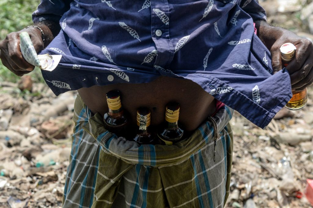 A man shows bottles of alcohol, stuck under his waistband, bought from a liquor shop after the government eased a nationwide lockdown imposed as a preventive measure against the COVID-19 coronavirus, on the outskirts of Chennai on May 7, 2020.(Photo by ARUN SANKAR/AFP via Getty Images)