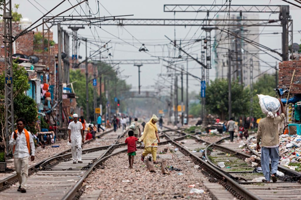 Residents walk along the train tracks in Azadpur area after the government eased a nationwide lockdown imposed as a preventive measure against the spread of the COVID-19 coronavirus, in New Delhi on June 26, 2020. (Photo by XAVIER GALIANA/AFP via Getty Images)