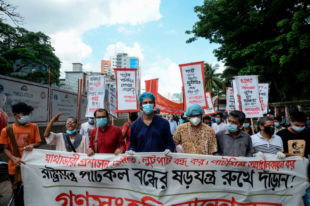 Bangladesh's left wing party supporters walk behind a banner during a protest against the shutdown of a state-owned jute mill in Dhaka on July 1, 2020. (Photo by MUNIR UZ ZAMAN/AFP via Getty Images)