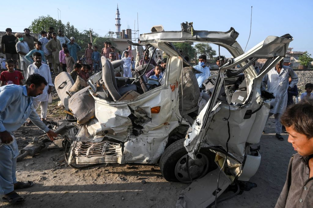 Residents gather around the wreckage of a van alongside a railway track following the accident between a train and the van transporting Sikh pilgrims in Farooqabad area in Sheikhupura district of the Pakistan's Punjab province on July 3, 2020. (Photo by ARIF ALI/AFP via Getty Images)
