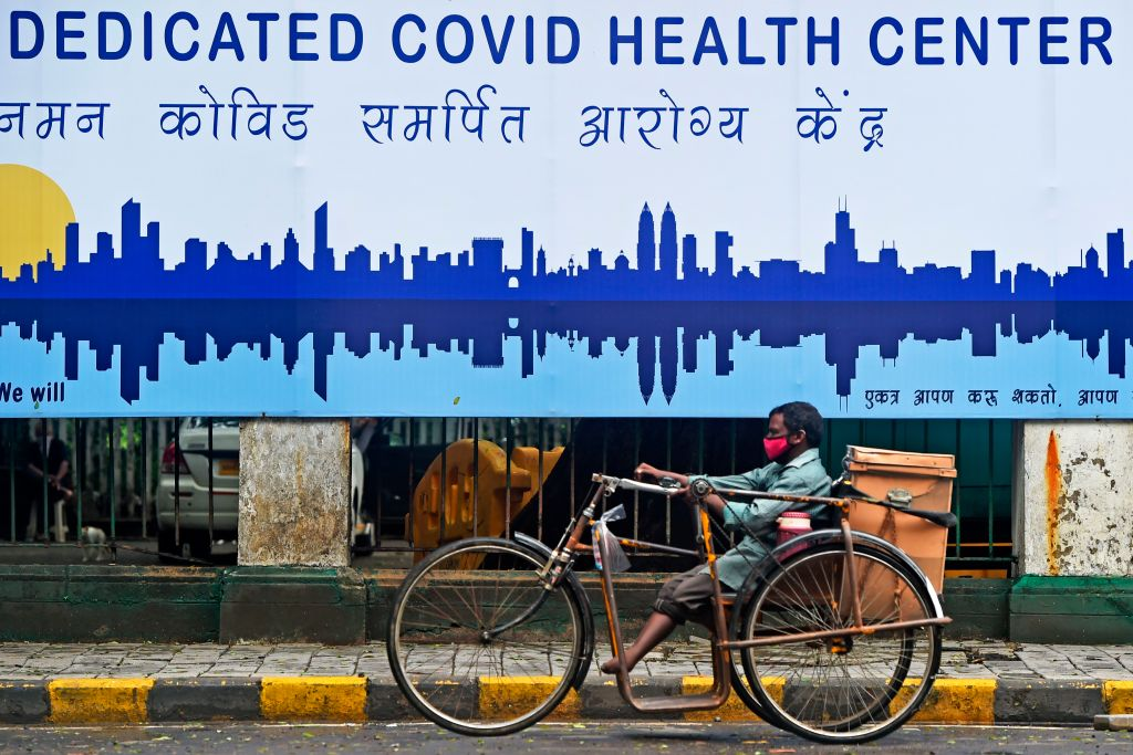 A physically challenged man rides a tricycle in front of a COVID-19 coronavirus health center in Mumbai on July 7, 2020. (Photo by PUNIT PARANJPE/AFP via Getty Images)