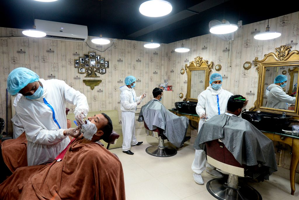 Barbers wearing protective cloths give to their clients a haircut at a barber shop amid concerns over the spread of the COVID-19 coronavirus, in Dhaka on July 7, 2020. (Photo by MUNIR UZ ZAMAN/AFP via Getty Images)