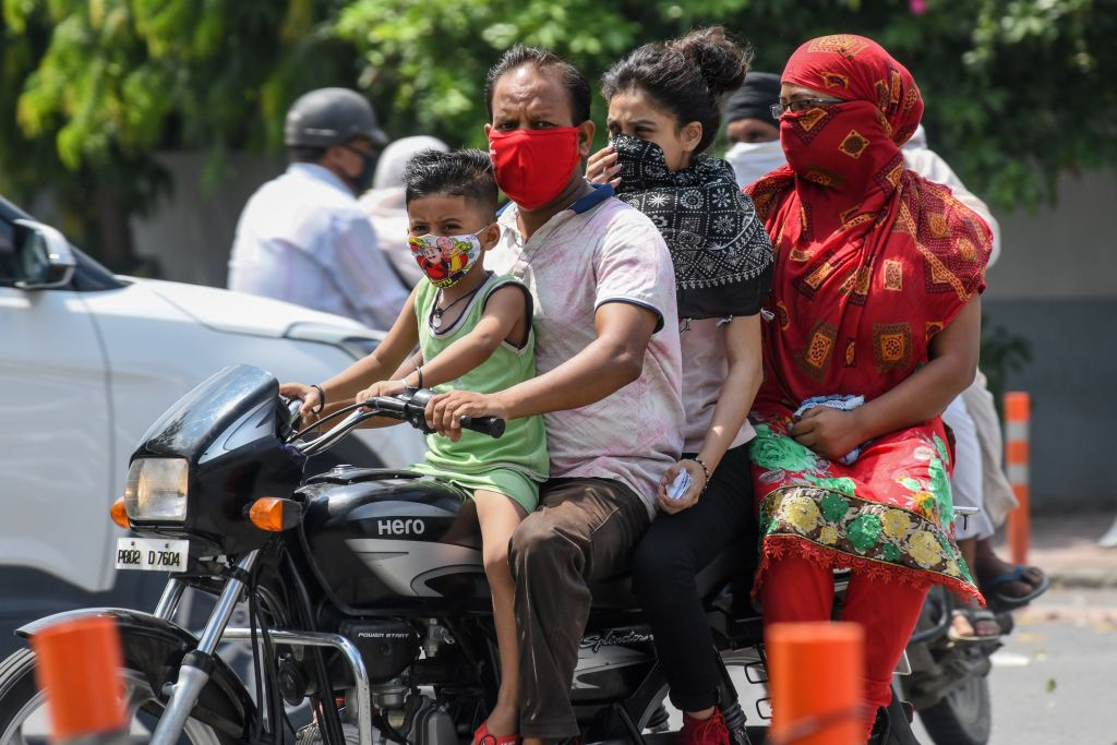 A boy and a man wear facemasks as a preventive measure against the COVID-19 coronavirus while riding with their family on a motorbike in Amritsar on July 8, 2020. (Photo by NARINDER NANU/AFP via Getty Images)