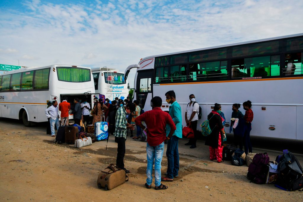 People wait to board buses and return to their home towns at the Karnataka-Tamil Nadu state border on the outskirts of Bangalore on July 13, 2020, as another lockdown is underway in Bangalore in an attempt to contain the surge of COVID-19 coronavirus cases. (Photo by MANJUNATH KIRAN/AFP via Getty Images)