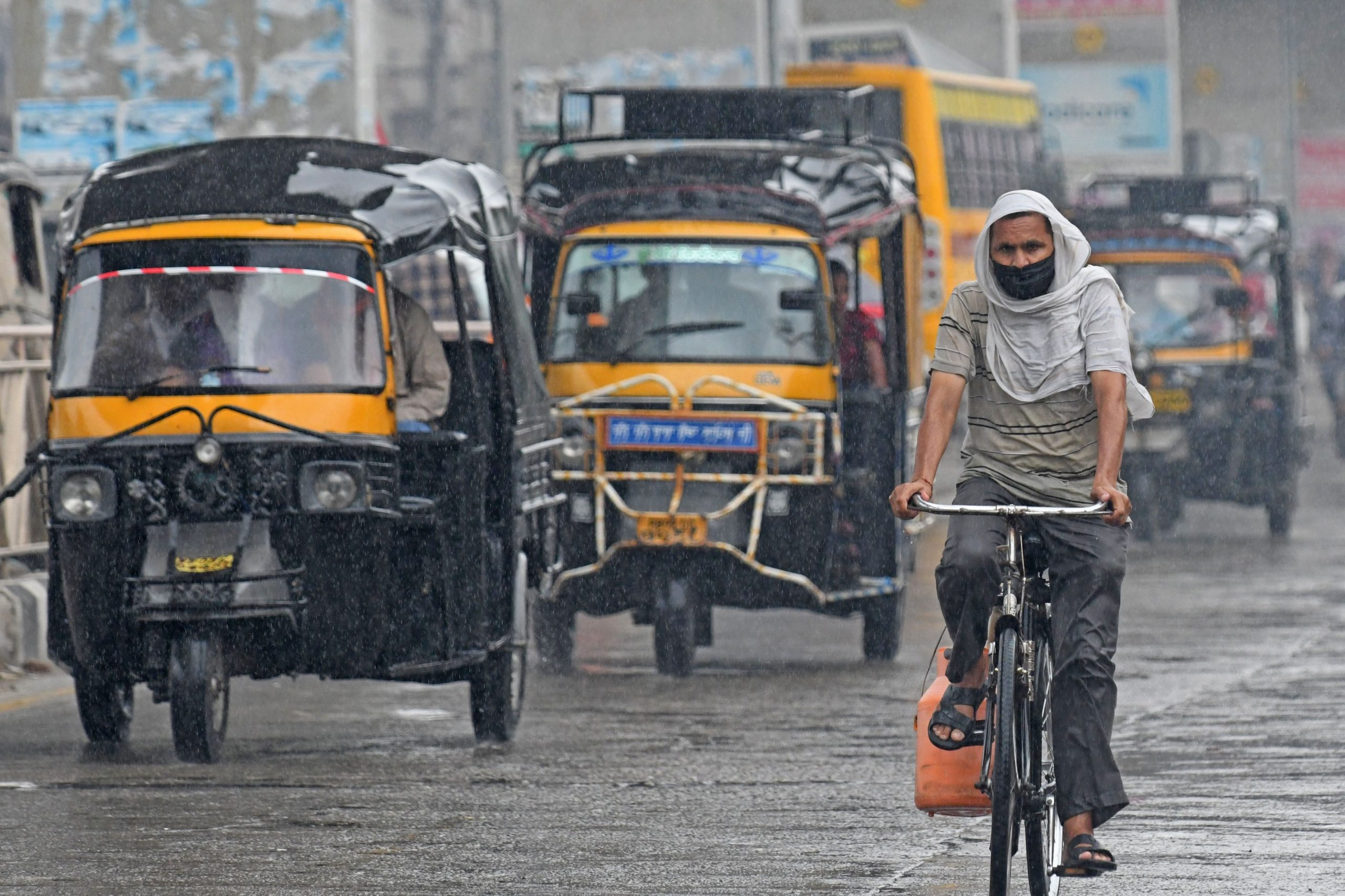 A man rides a bicycle on a busy road during a rain shower in Amritsar on July 21, 2020. - Torrential rains during the monsoon season between June and September trigger floods, landslides and lightning strikes across the region, with hundreds dying every year. (Photo by NARINDER NANU / AFP) (Photo by NARINDER NANU/AFP via Getty Images)
