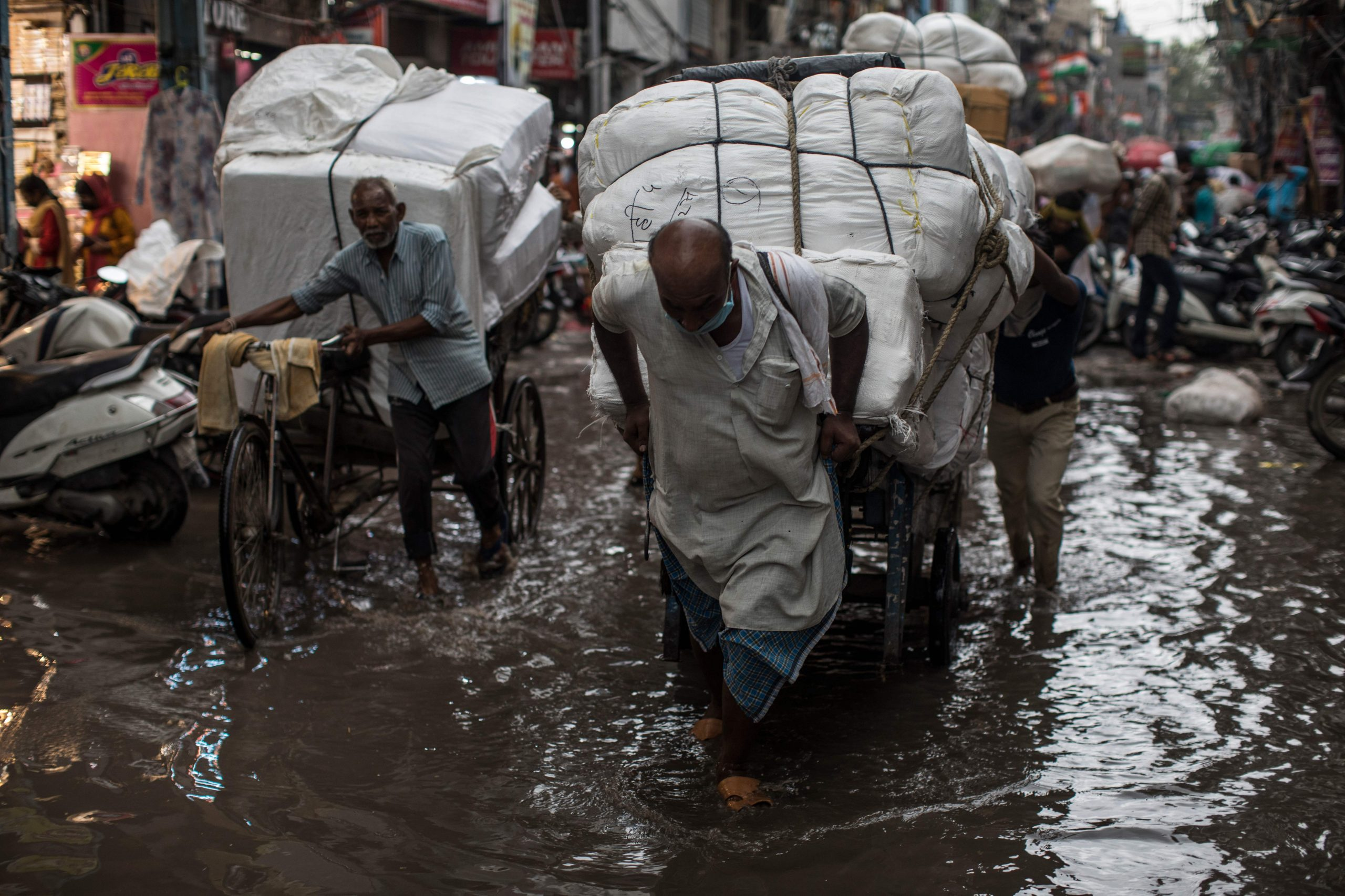 Labourers wade along a flooded street while pulling a handcart and a rickshaw (L) after a monsoon rainfall in New Delhi on July 29, 2020. (Photo by Xavier GALIANA / AFP) (Photo by XAVIER GALIANA/AFP via Getty Images)