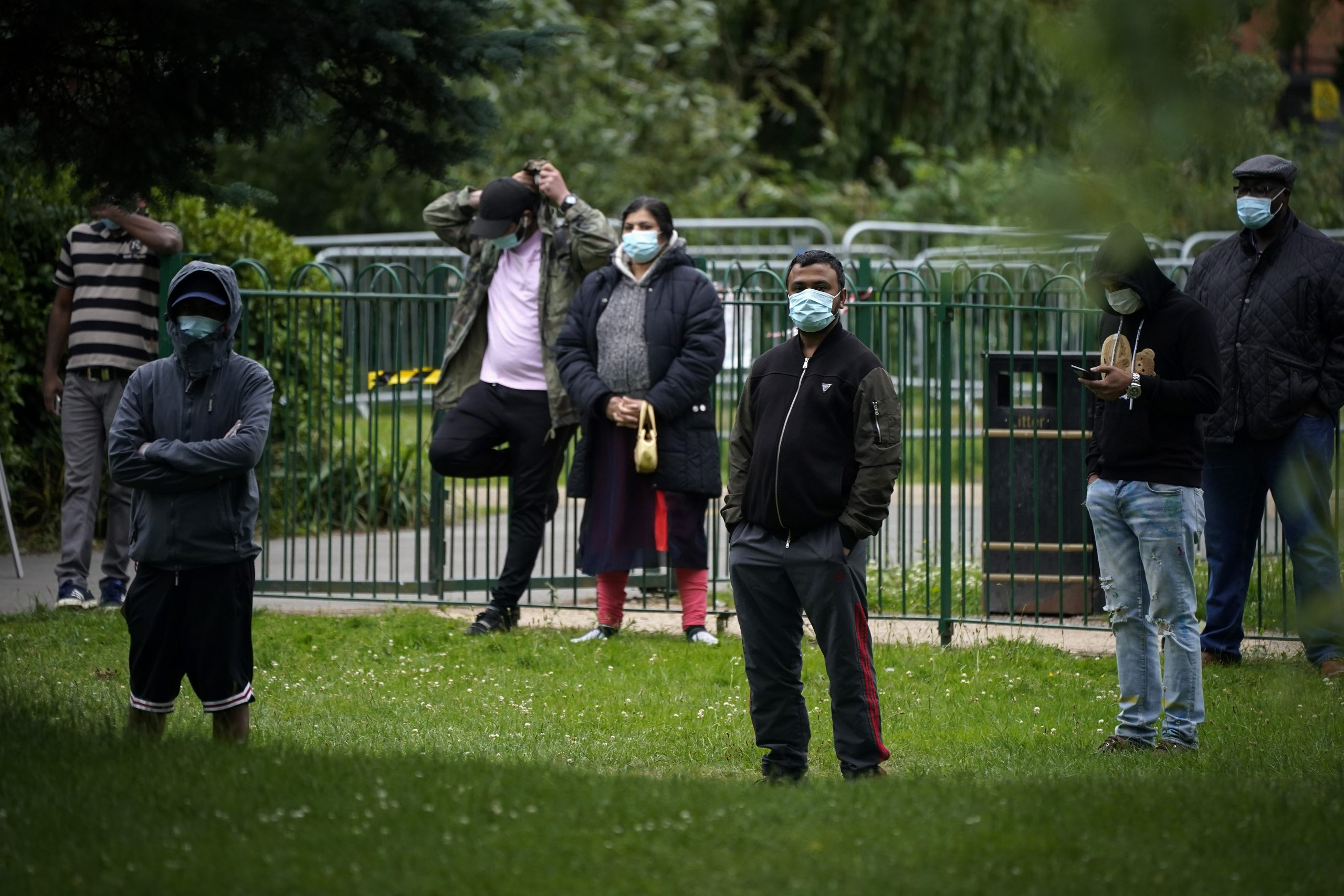 LEICESTER, ENGLAND - JUNE 29: People in face masks queue at a walk in coronavirus testing centre at Spinney Park on June 29, 2020 in Leicester, England. In a television appearance on Sunday, British Home Secretary Priti Patel confirmed the government was considering a local lockdown after a spike in coronavirus cases in the city. The city's mayor has said that Pubs and restaurants in Leicester may stay closed for two more weeks due to a recent surge in coronavirus cases. (Photo by Christopher Furlong/Getty Images)