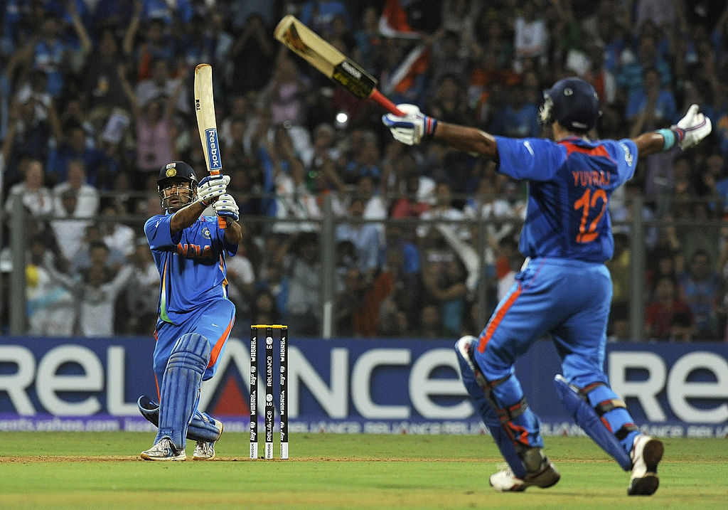 Indian captain Mahendra Singh Dhoni (L) hits a six to win against Sri Lanka as teammate Yuvraj Singh reacts during the Cricket World Cup 2011 final at The Wankhede Stadium in Mumbai on April 2, 2011. India beat Sri Lanka by six wickets. (Photo: INDRANIL MUKHERJEE/AFP via Getty Images)