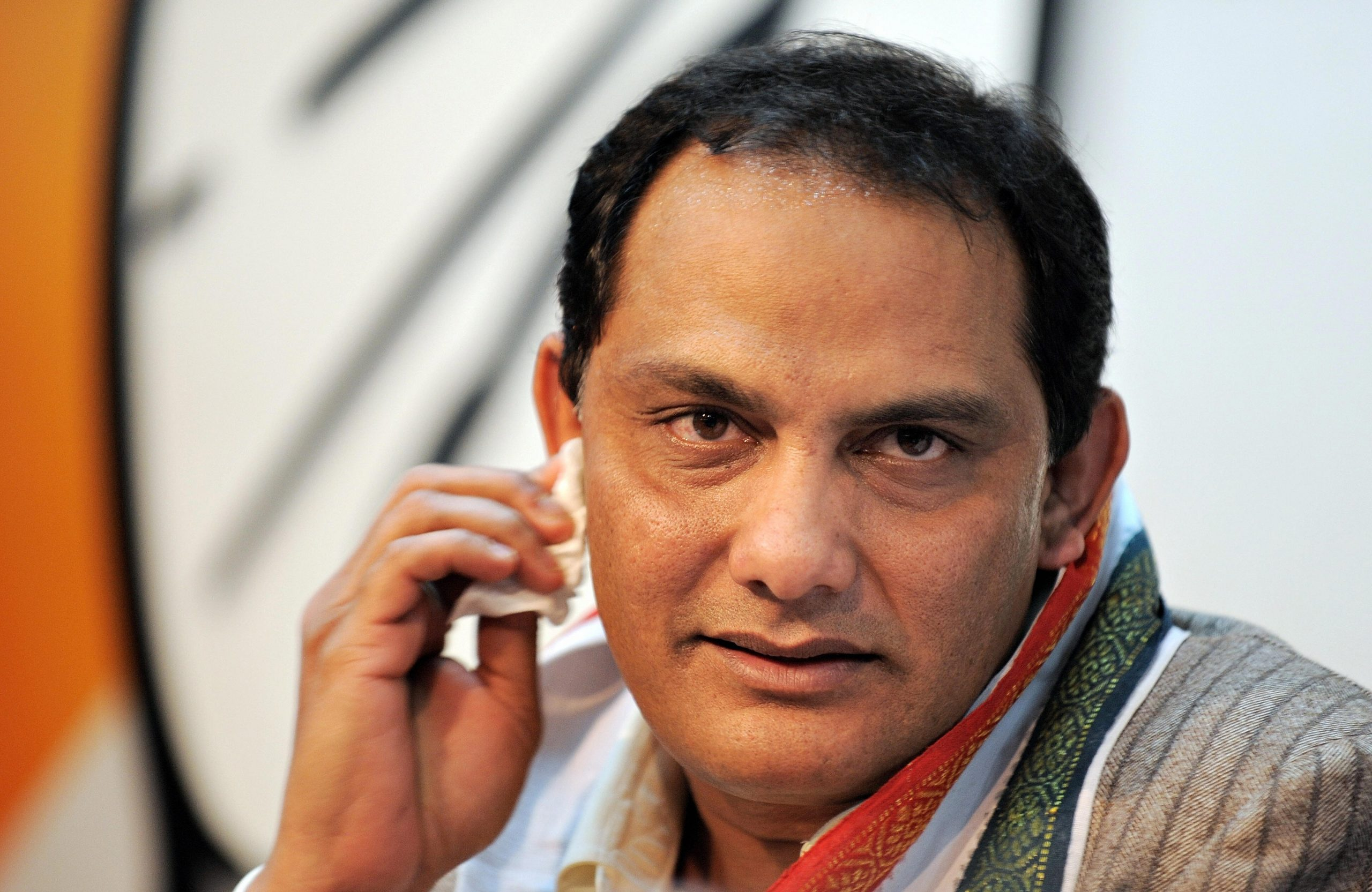 Former India cricket captain Mohammad Azharuddin wipes sweat from his face while addressing mediapersons at the Congress party headquarters in New Delhi on February 19, 2009. Former India cricket captain Mohammad Azharuddin, who was forced to quit the game after a match-fixing scandal, entered the country's turbulent political scene on February 19. Azharuddin, 46, was paraded for the media at the Congress headquarters in New Delhi after joining the ruling party ahead of upcoming parliamentary elections.   AFP PHOTO/ MANAN VATSYAYANA (Photo credit should read MANAN VATSYAYANA/AFP via Getty Images)