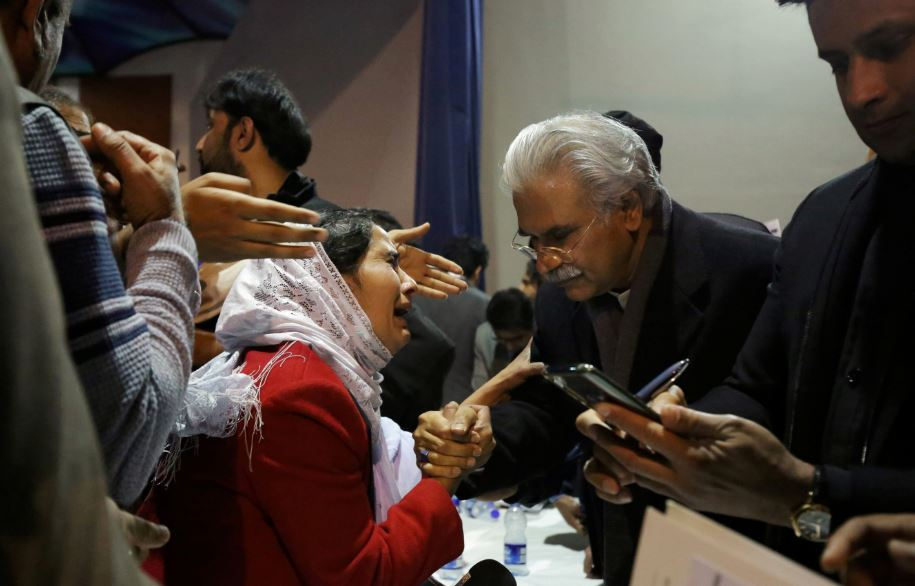FILE PHOTO: Pakistan's Health Minister, Zafar Mirza (R), interacts with the mother of a Pakistani student, who is stuck in the locked down Hubei province at the center of China's coronavirus outbreak, as people demand evacuation of their children during a meeting in Islamabad, Pakistan February 19, 2020. REUTERS/Saiyna Bashir/File Photo