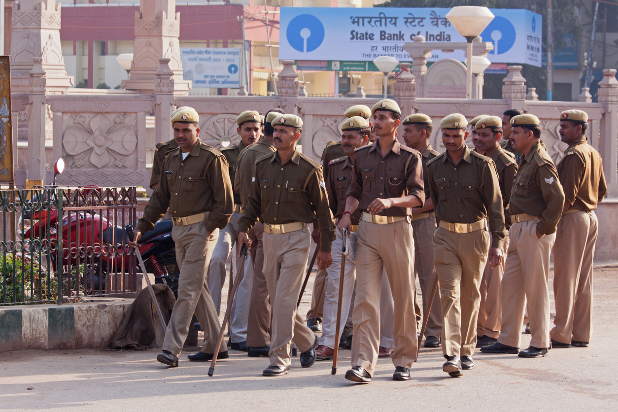 VARANASI, INDIA – MARCH 4, 2015: Local police carrying lathis marching through the city's streets providing security cover on the occasion of a visit by the Chief Minister of the Indian government