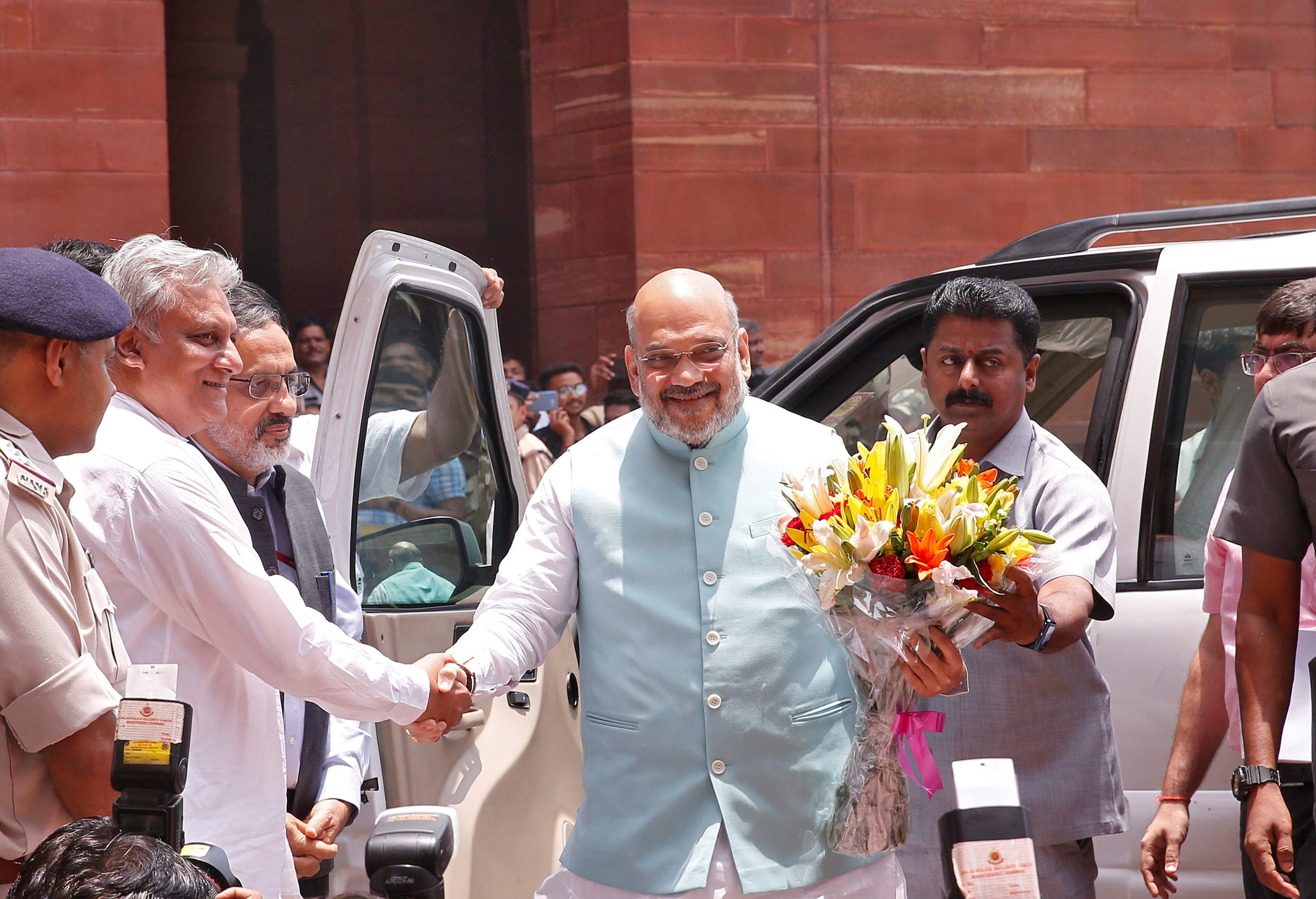 India's Home Minister Amit Shah receives a flower bouquet upon his arrival at the home ministry in New Delhi, India, June 1, 2019. REUTERS/Altaf Hussain/File Photo