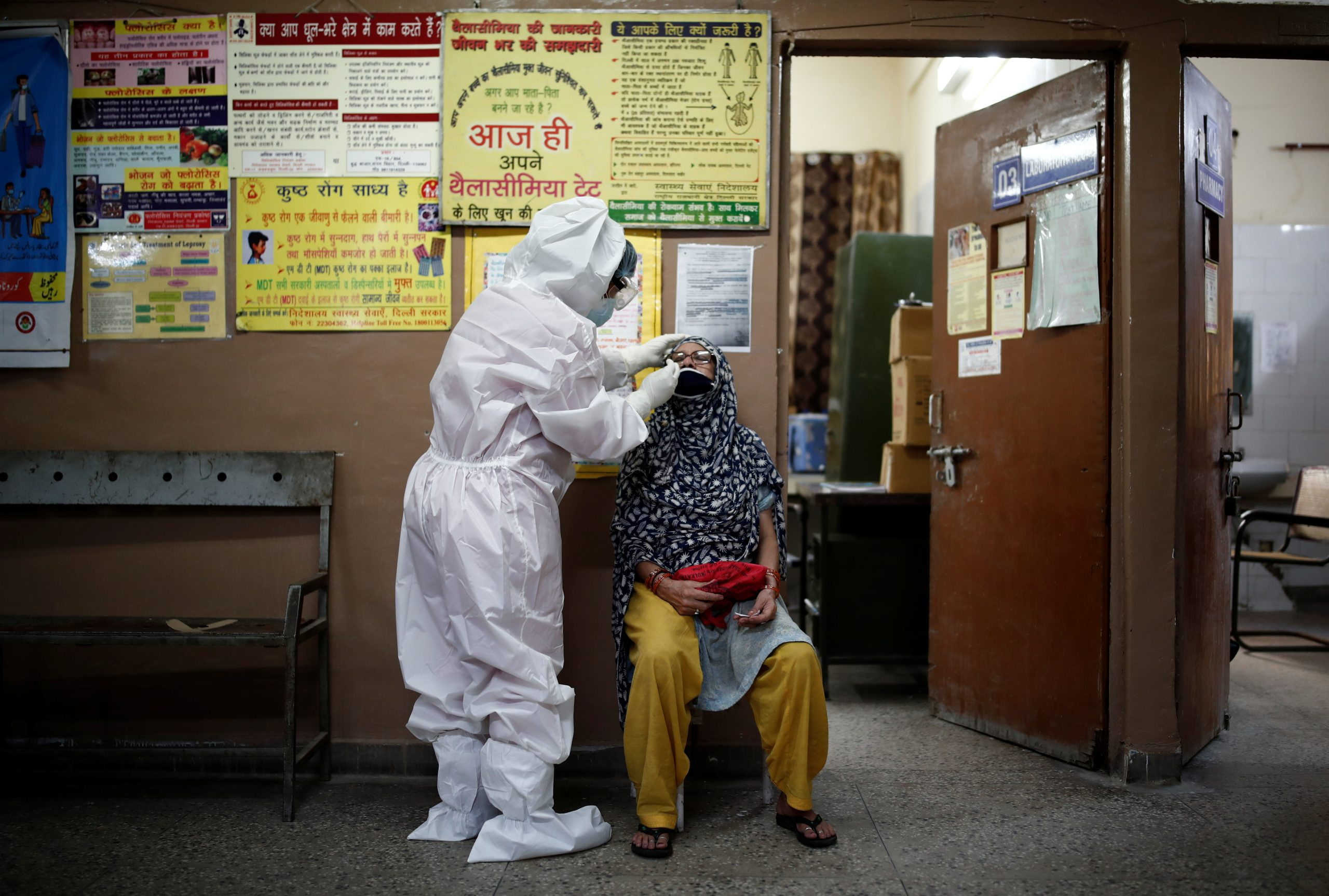 A health worker in personal protective equipment (PPE) collects a sample using a swab from a person at a local health centre to conduct tests for the coronavirus disease (COVID-19) in New Delhi, India August 7, 2020. REUTERS/Adnan Abidi