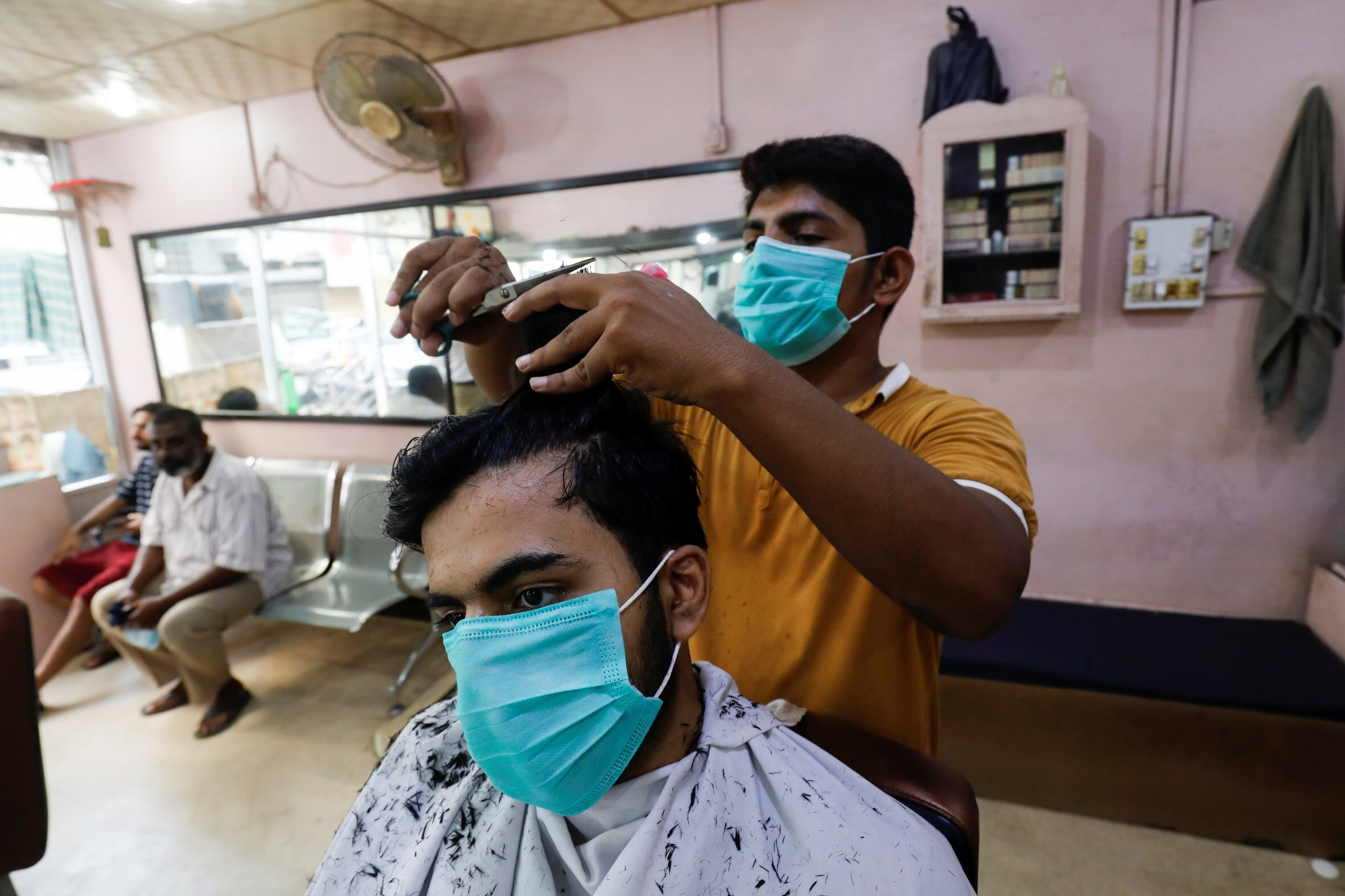 A man wears a protective mask as he has a haircut at a barbershop, after Pakistan lifted lockdown restrictions, as the coronavirus disease (COVID-19) outbreak continues, in Karachi, Pakistan August 10, 2020. REUTERS/Akhtar Soomro