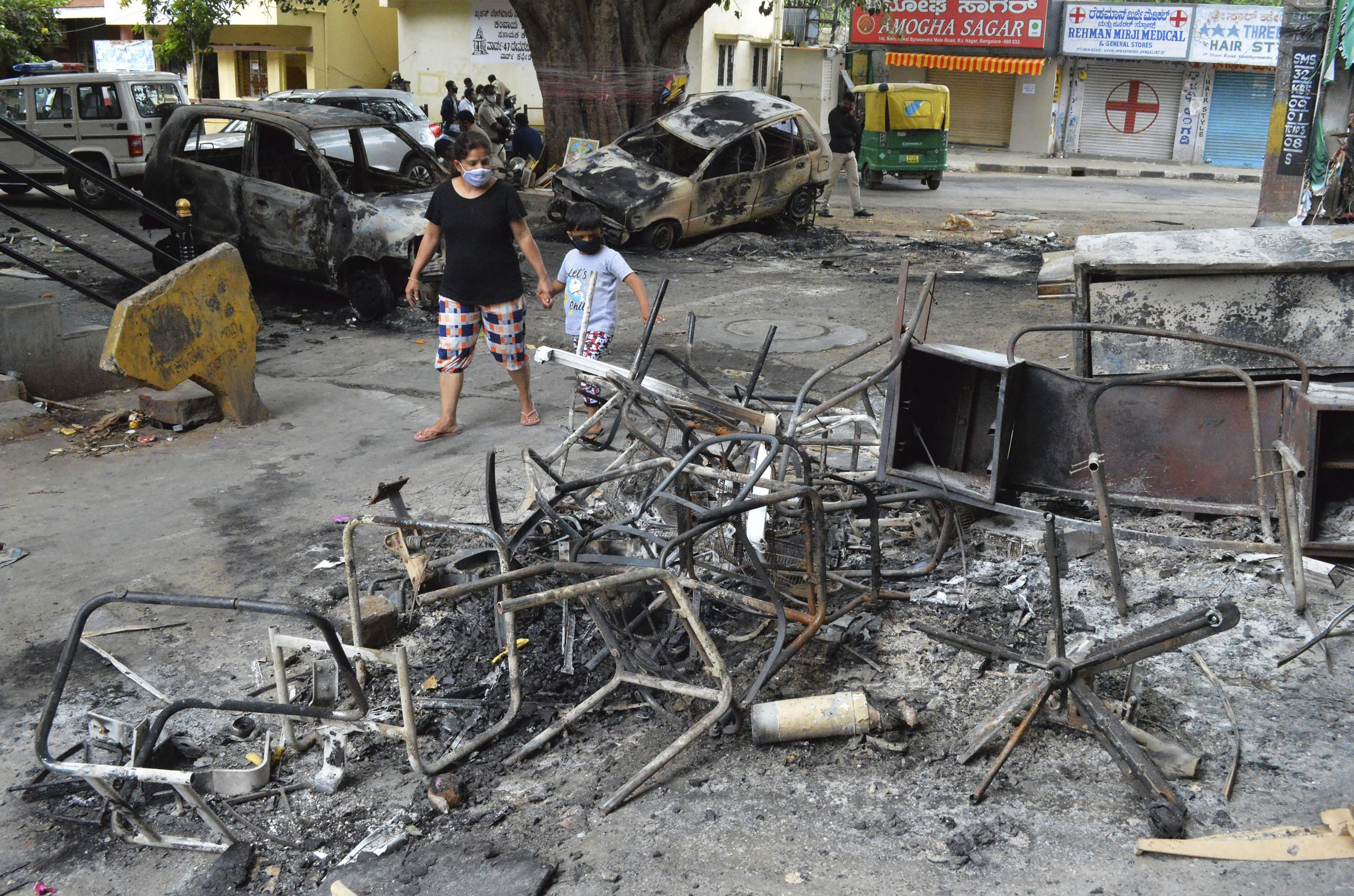 A woman and a child walks past the wreckage of vehicles and furniture burnt during violent protests in Bengaluru, India, Wednesday, Aug. 12, 2020.  (AP Photo)