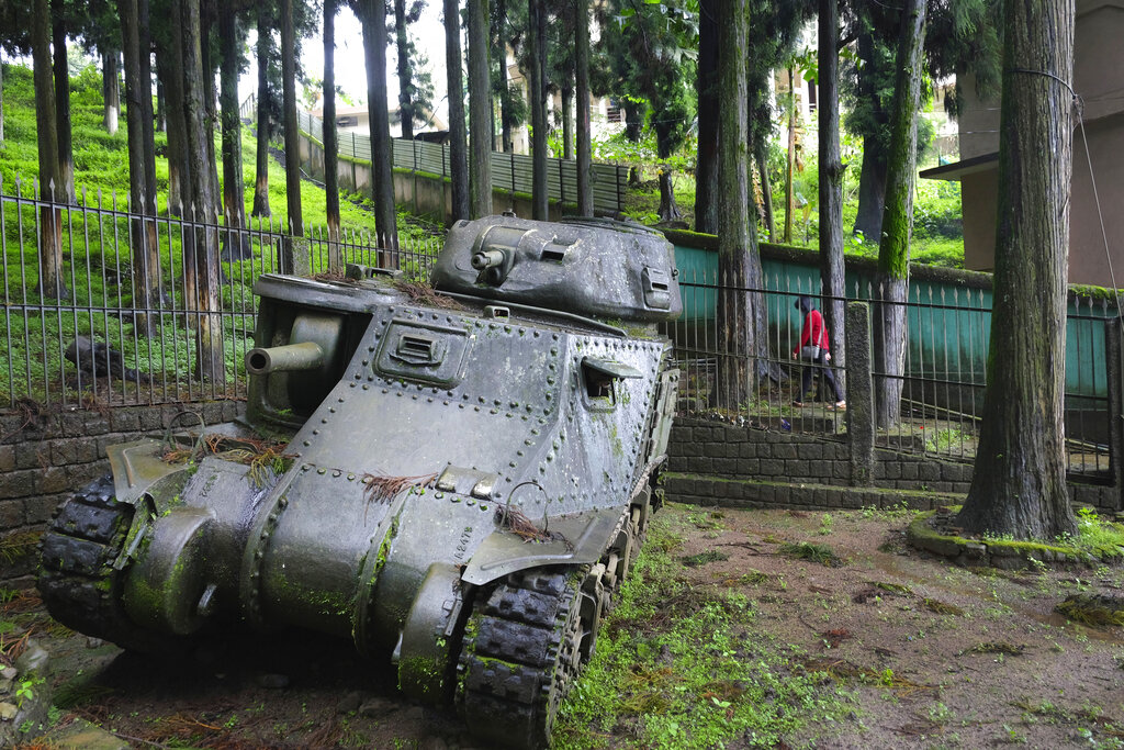 A woman walks past a Medium Tank M3 Grant that was abandoned when it went down this hill and crashed against a tree while climbing the Kohima Ridge to support British troops of the 2nd Division on May 6, 1944, in Kohima, India, Thursday, Aug. 13, 2020. In April 1944, 15,000 men from the 31st Division of Japan's Imperial Army commanded by General Sato arrived with the aim of taking over Kohima, a hill town that was also the headquarters of the British in the Naga Hills. The hill station, on the Indian border with Myanmar, was considered strategically important for Japanese advancement into India. The tank has been preserved in the exact position where it was abandoned. (AP Photo/Yirmiyan Arthur)