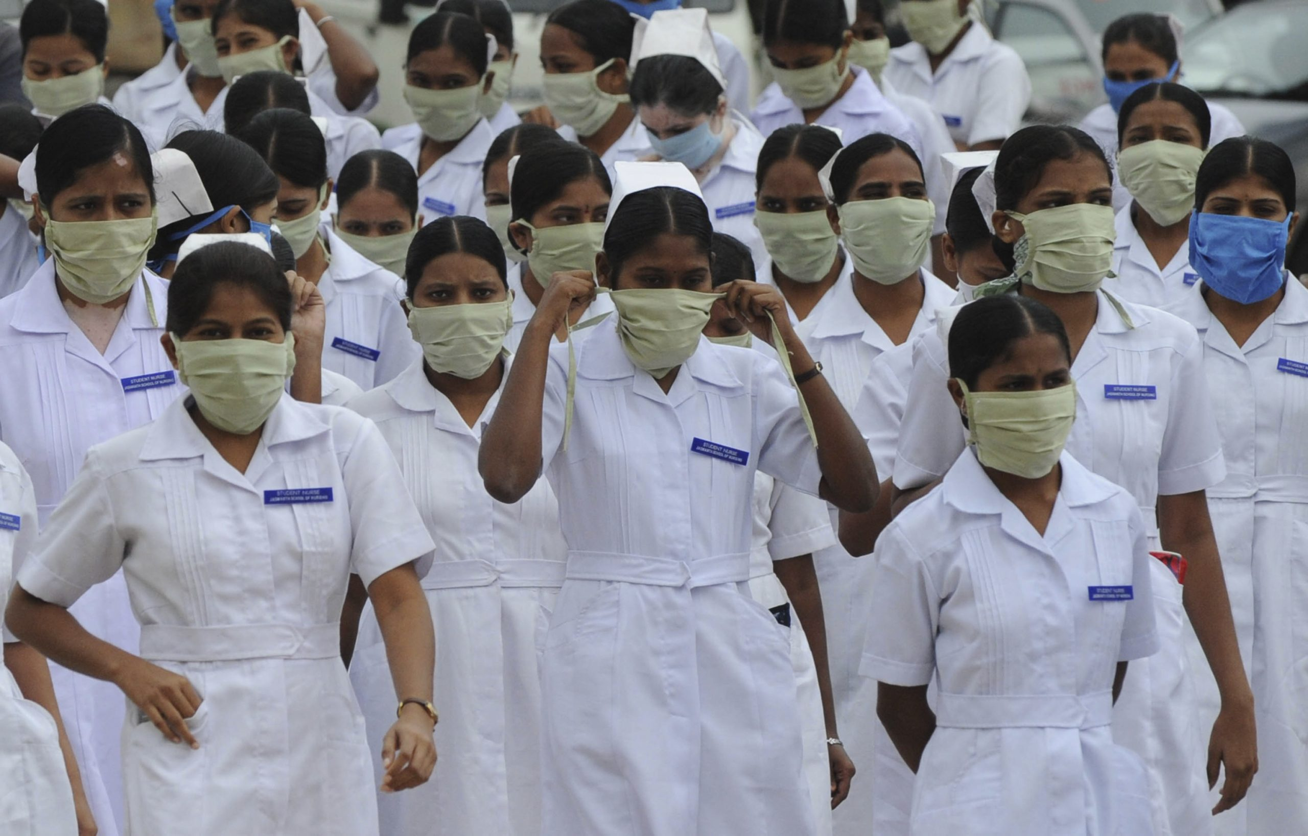 Indian nursing students wear masks at the Government Gandhi Hospital in Hyderabad on August 7, 2010. Health authorities confirmed that 15 more persons have tested positive for Swine Flu in the twin cities area of Hyderabad, local reports said. Six out of 21 nurses admitted to the hospital have tested positive for H1N1. AFP PHOTO/Noah SEELAM (Photo credit should read NOAH SEELAM/AFP via Getty Images)