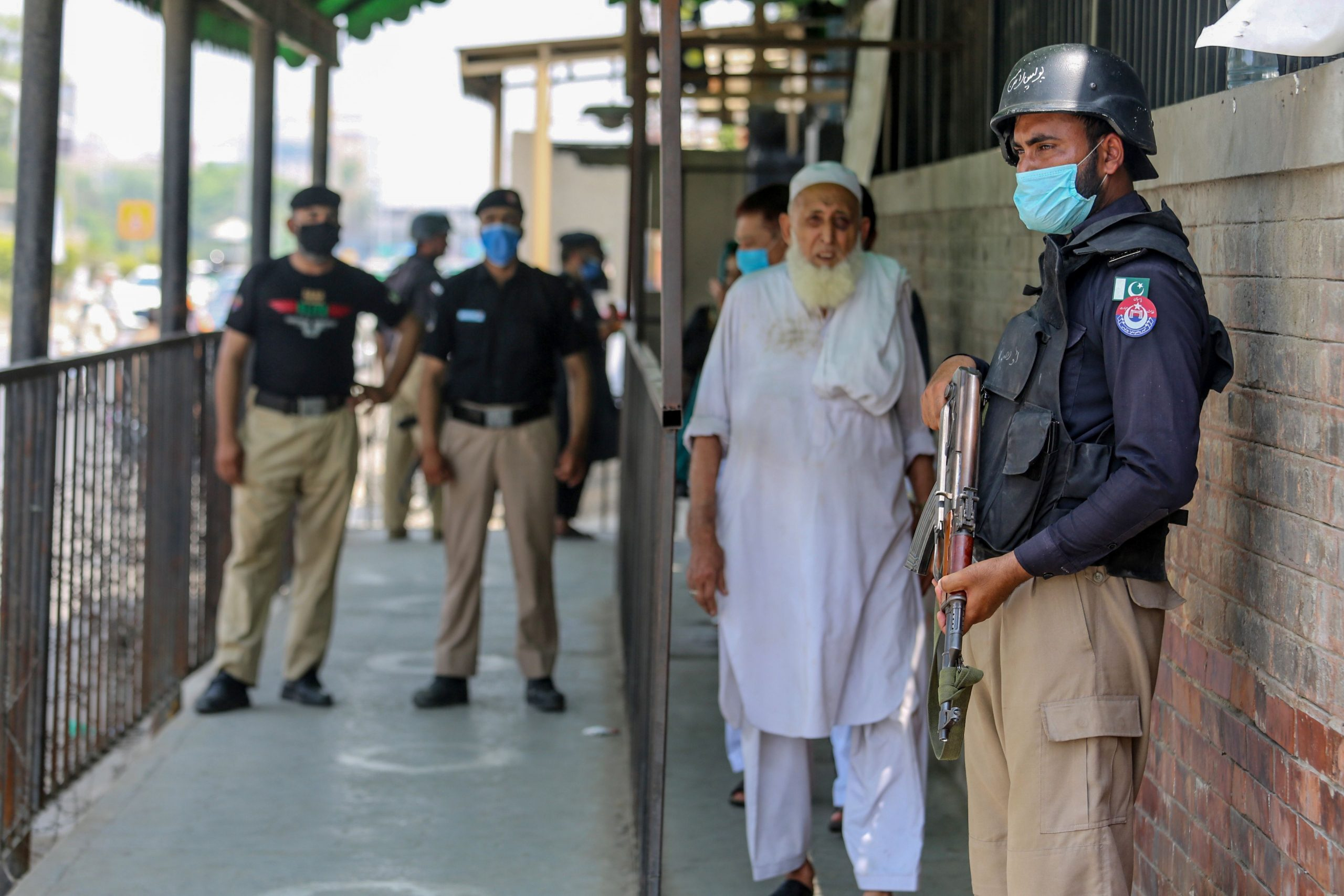Security personnel (L and R) stand guard outside the district court building following the killing of a man allegedly accused of blasphemy in Peshawar on July 29, 2020. - A man from a persecuted Islamic sect was killed by an assailant in a Pakistani courtroom on July 29 ahead of his hearing on blasphemy charges, police said. (Photo by - / AFP) / To go with 'PAKISTAN-UNREST-RELIGION-MINORITY' (Photo by -/AFP via Getty Images)