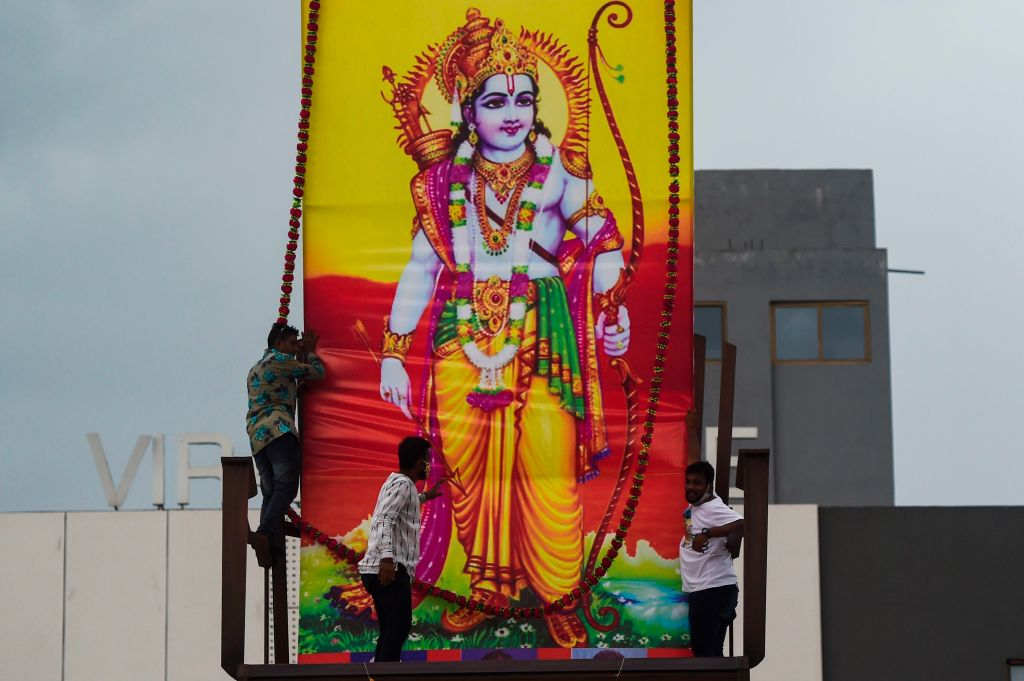Workers erect a large poster of Hindu Lord Ram on the roof of a service station in Vadodara, Gujarat, on August 5, 2020, to celebrate the groundbreaking ceremony of the Ram Temple in Ayodhya. (Photo by PUNIT PARANJPE/AFP via Getty Images)