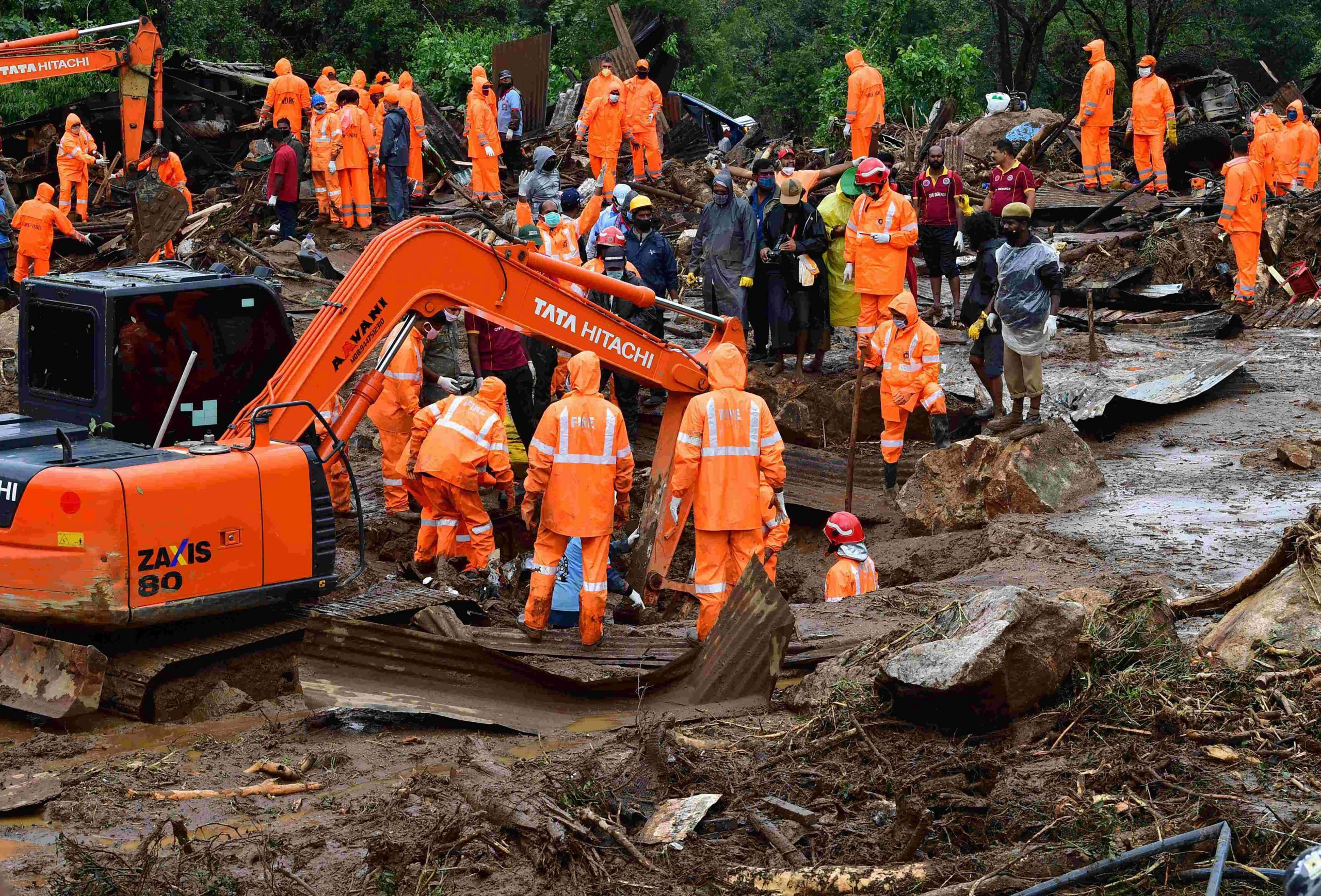 Rescue workers search for missing people at a landslide site caused by heavy rains in Pettimudy, in Kerala state, on August 8, 2020. (Photo by STR / AFP)