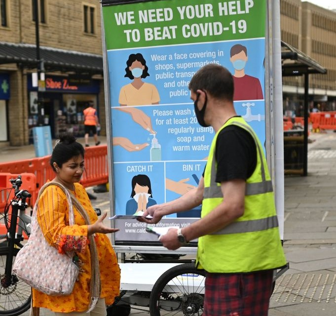 Leaflets are handed out beside a promotion funded by Calderdale Council -- an ad bike display advising people on how to slow the spread of the coronavirus, in Halifax in northern England on August 9, 2020. (Photo: OLI SCARFF/AFP via Getty Images)