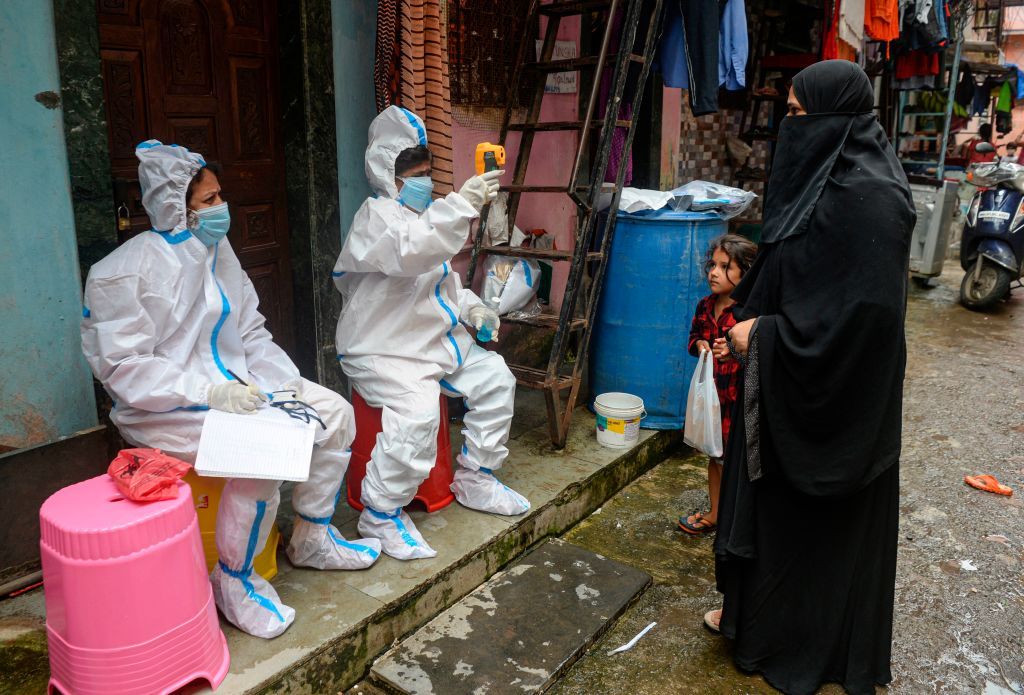 Health workers check the temperature of residents during a Covid-19 screening in the Dharavi slum, in Mumbai on August 11, 2020. (Photo: INDRANIL MUKHERJEE/AFP via Getty Images)