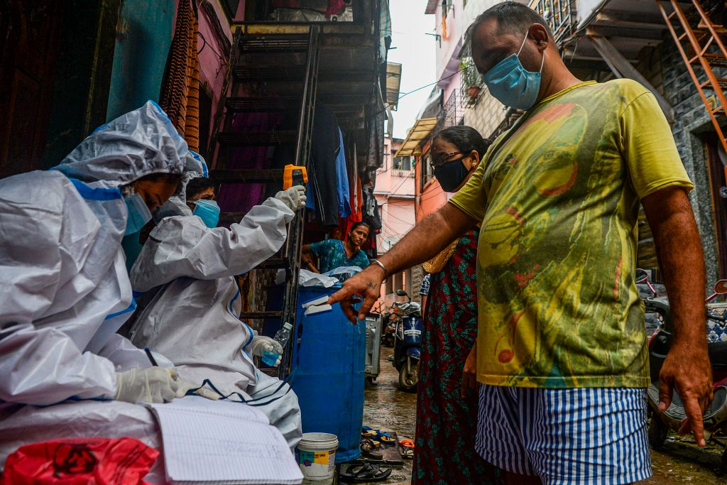 Health workers wearing Personal Protective Equipments (PPE) check the temperature and the oxygen level of residents during a COVID-19 coronavirus screening in the Dharavi slum, in Mumbai on August 11, 2020. (Photo by INDRANIL MUKHERJEE/AFP via Getty Images)