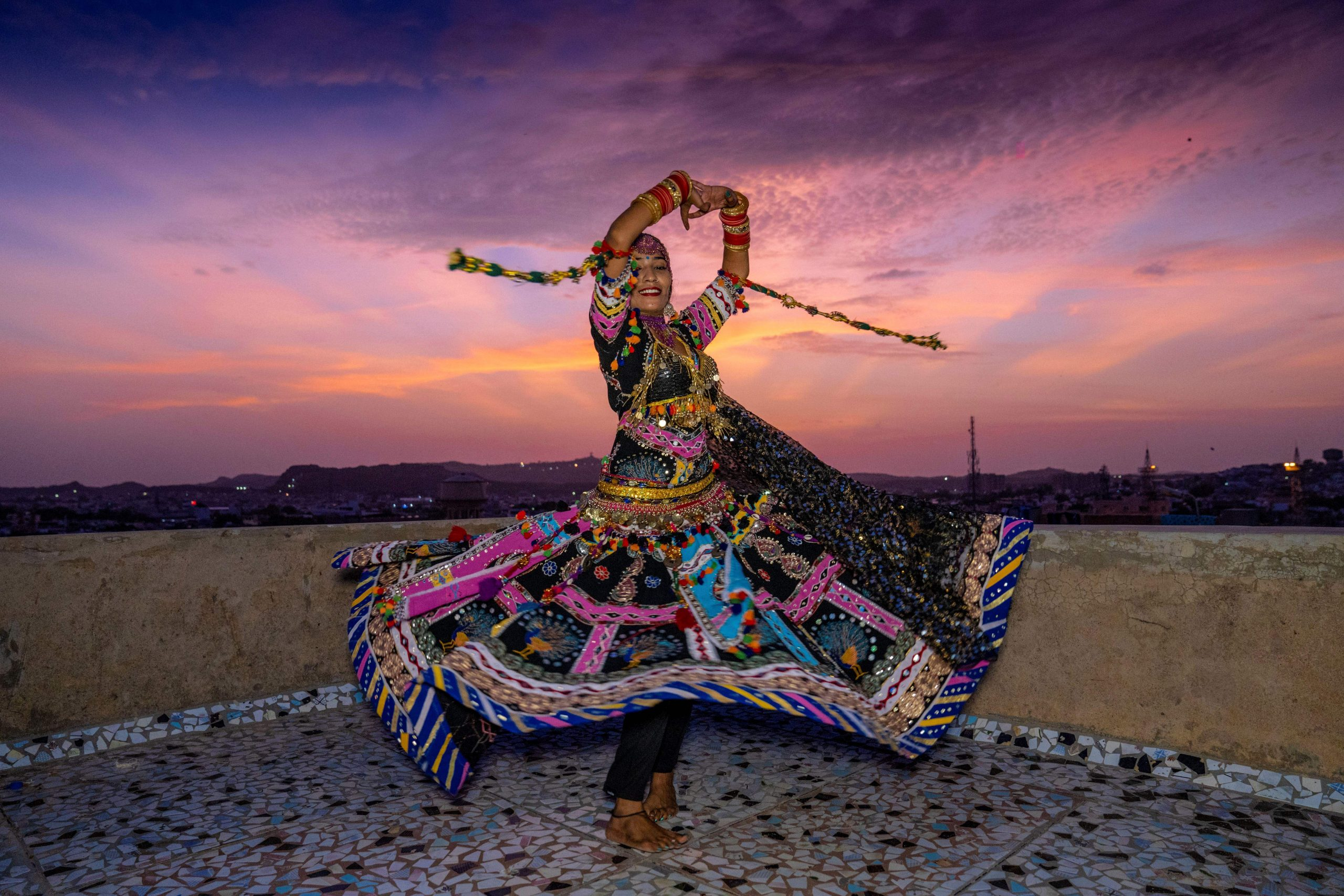 """In this picture taken on August 13, 2020, Kalbeliya gypsy dancer Aasha Sapera practices before hosting online dance classes amid the COVID-19 coronavirus pandemic in Jodhpur. - The coronavirus pandemic has forced many people to go online, but the largely nomadic, marginalised Kalbeliya face bigger challenges than most, with several living in mud huts or tents with patchy electricity and non-existent WiFi. """"In the beginning, I had no idea how to make this work,"""" dancer Aasha Sapera told AFP, describing her early forays into hosting classes on Zoom. (Photo by Sunil VERMA / AFP) / To go with AFP story 'INDIA-HEALTH-VIRUS-DANCE-COMMUNITIES-TRADITION-TECH' feature by Ammu Kannampilly and Sunil Verma (Photo by SUNIL VERMA/AFP via Getty Images)"""