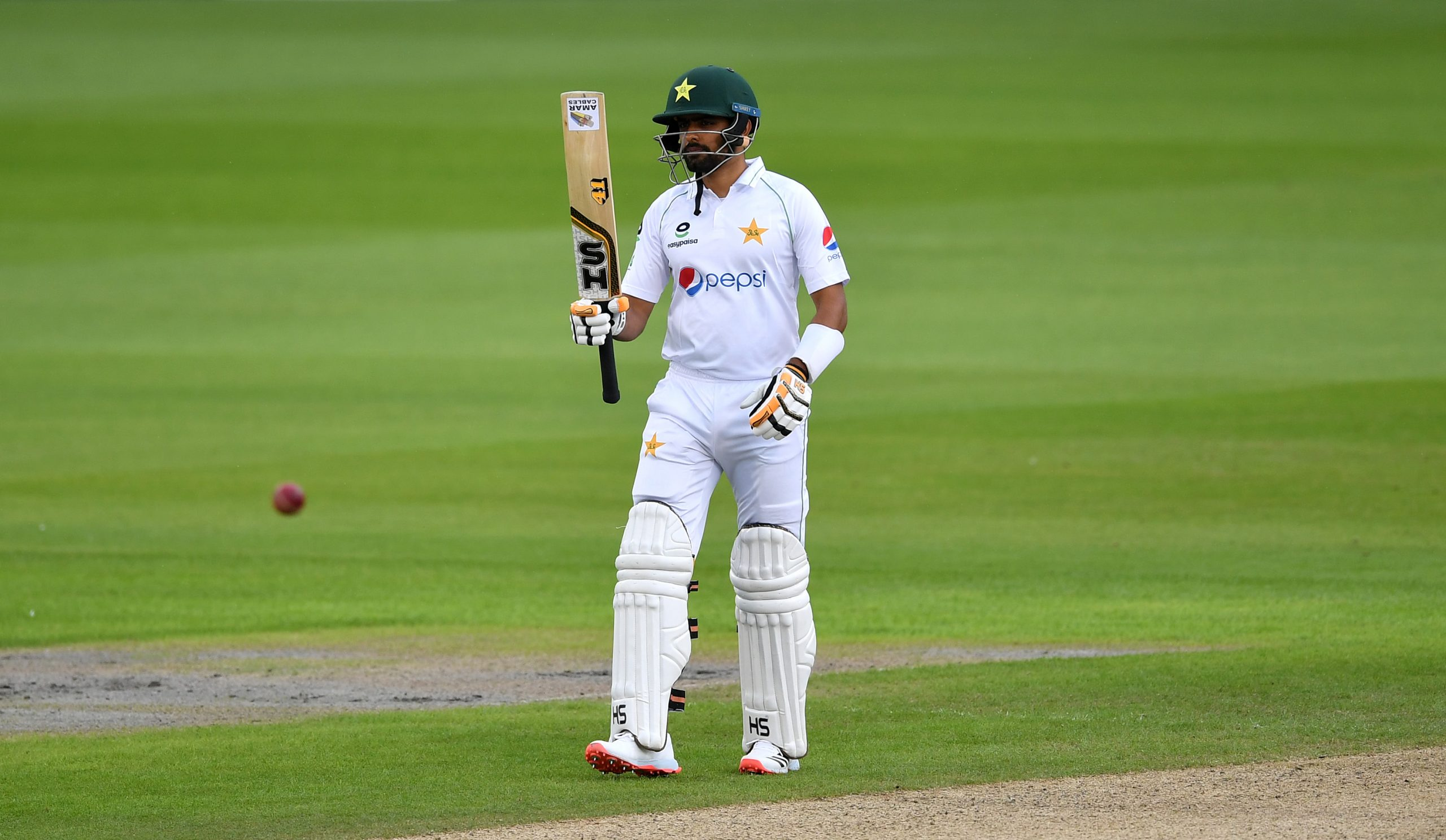 MANCHESTER, ENGLAND - AUGUST 05: Babar Azam of Pakistan celebrates reaching fifty  during Day One of the 1st #RaiseTheBat Test Match between England and Pakistan at Emirates Old Trafford on August 05, 2020 in Manchester, England. (Photo by Dan Mullan/Getty Images)