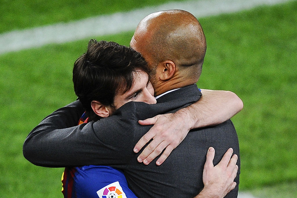 FILE PHOTO: Lionel Messi of FC Barcelona (L) hugs his Head coach Josep Guardiola of FC Barcelona after scoring his team's third goal during the La Liga match between FC Barcelona and RCD Espanyol at Camp Nou on May 5, 2012 in Barcelona, Spain. (Photo by David Ramos/Getty Images)
