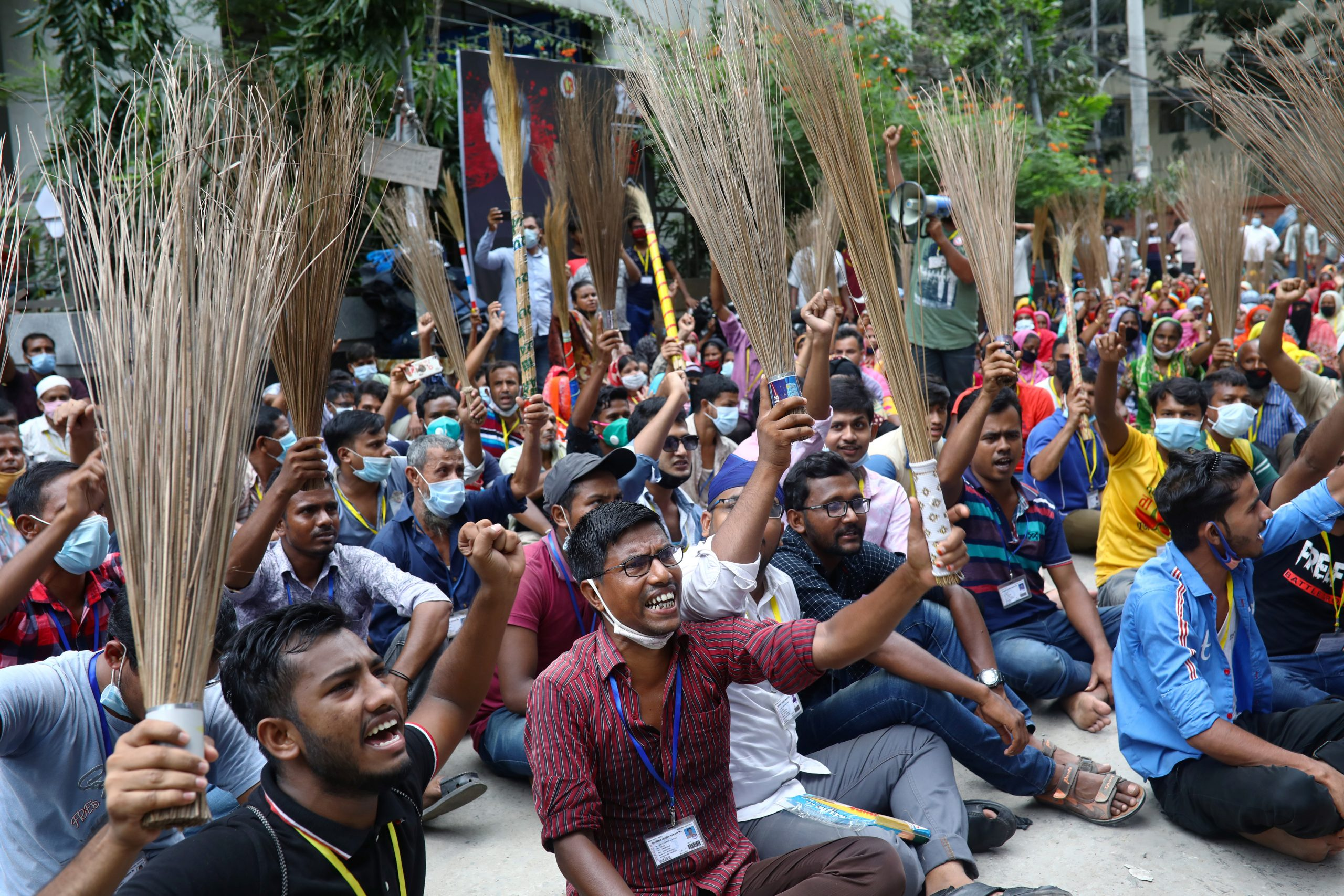 Garment workers shout slogans while holding brooms during a protest demanding their due wages in Dhaka, Bangladesh, September 7, 2020. REUTERS/Mohammad Ponir Hossain