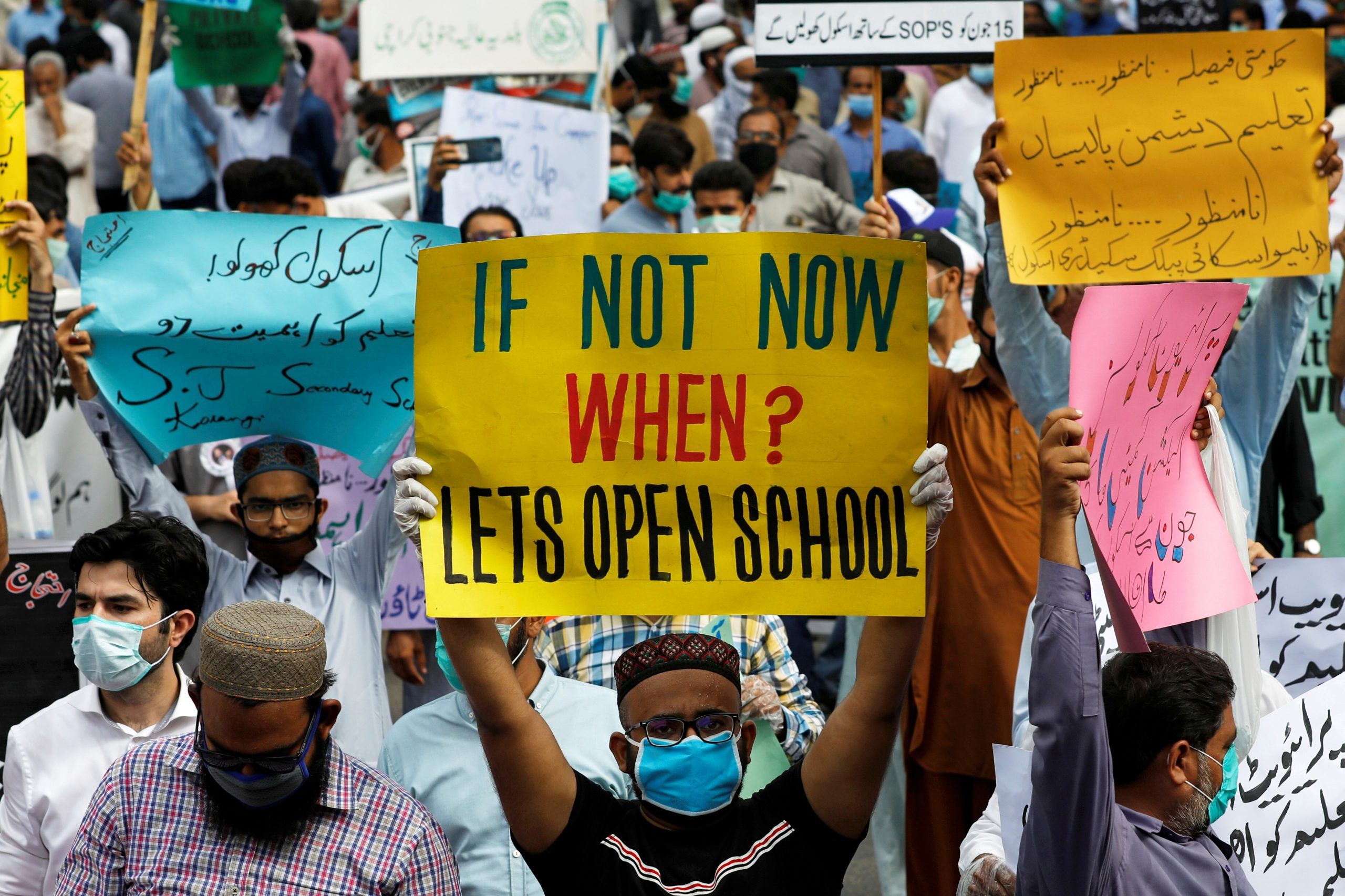 FILE PHOTO: Teachers of private schools wear protective masks as they hold signs during a protest demanding the opening of schools, which are closed due to the spread of the coronavirus disease (COVID-19), in Karachi, Pakistan June 10, 2020. REUTERS/Akhtar Soomro/File Photo