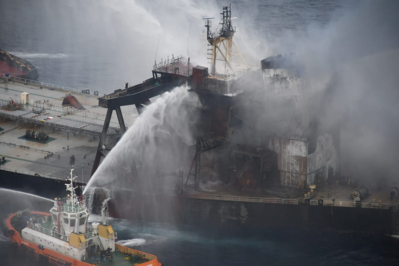 A Sri Lankan Navy boat sprays water on the New Diamond, a very large crude carrier (VLCC) chartered by Indian Oil Corp (IOC), that was carrying the equivalent of about 2 million barrels of oil, after a fire broke out off east coast of Sri Lanka September 8, 2020. Sri Lankan Airforce media/Handout via REUTERS