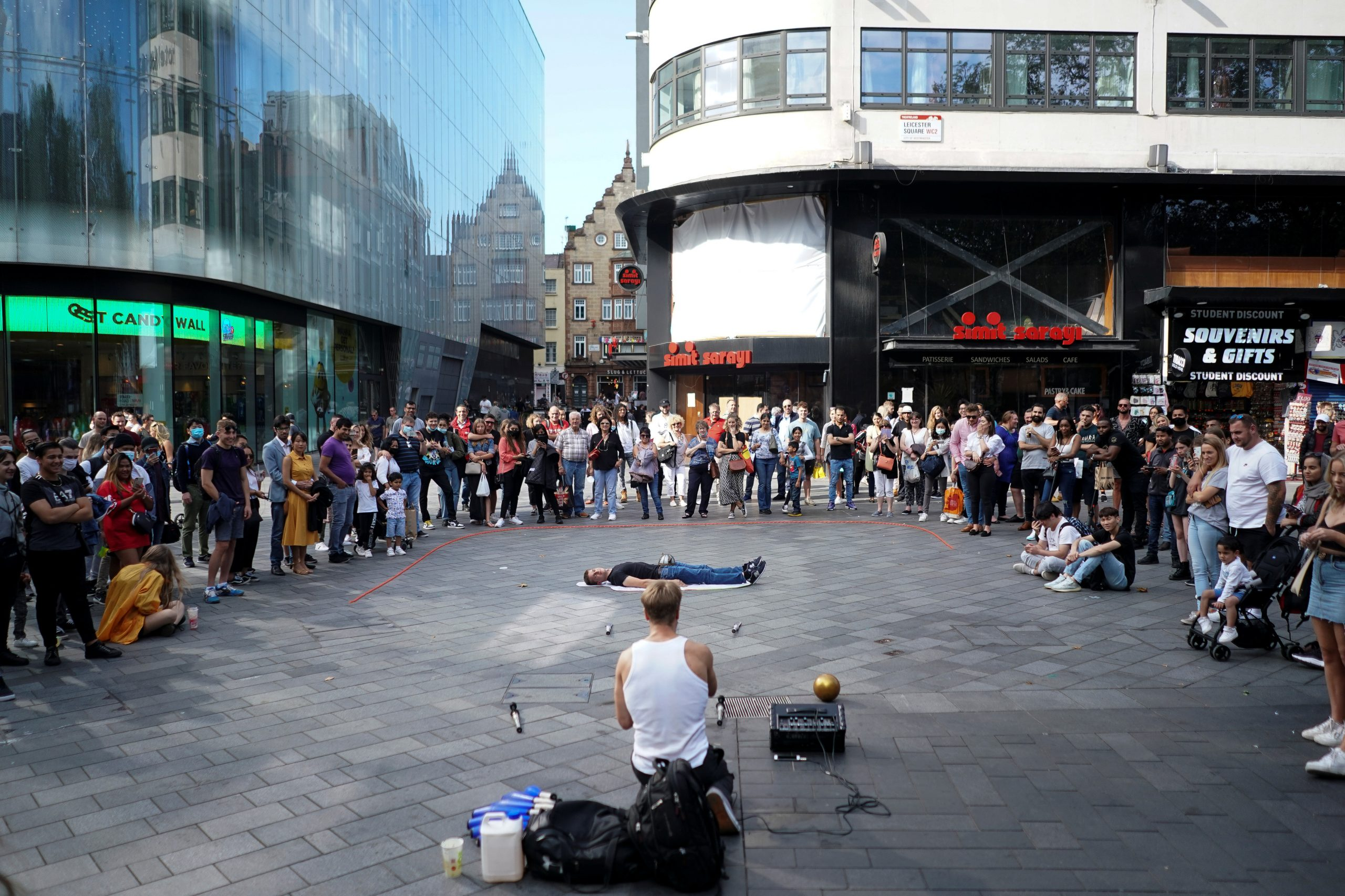 People watch a street performance in Leicester Square, amid fears of a second coronavirus wave, on September 20, 2020. (REUTERS/Henry Nicholls)