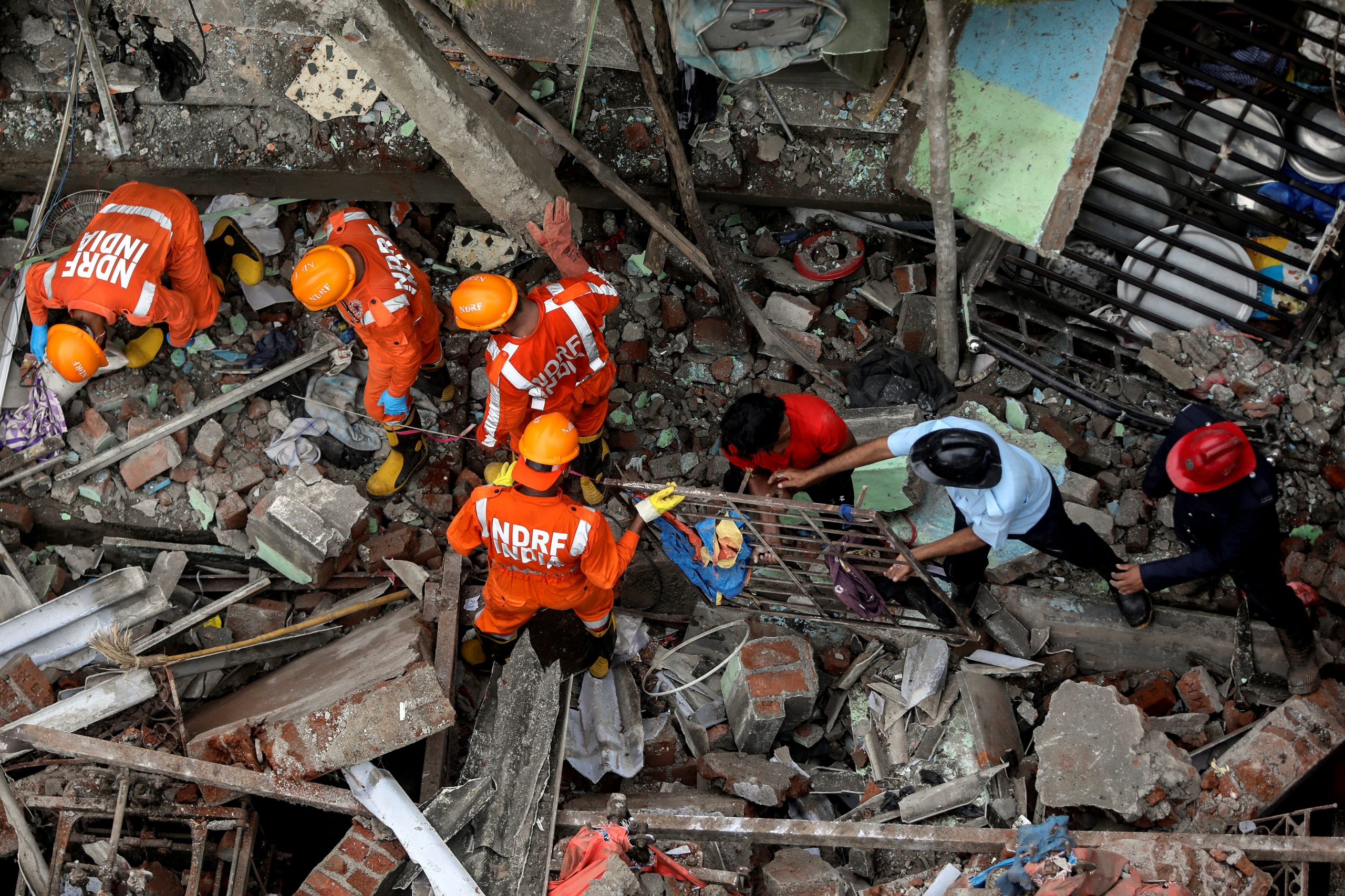 National Disaster Response Force (NDRF) officials and firemen remove debris as they look for survivors after a three-storey residential building collapsed in Bhiwandi on the outskirts of Mumbai, India, September 21, 2020. REUTERS/Francis Mascarenhas