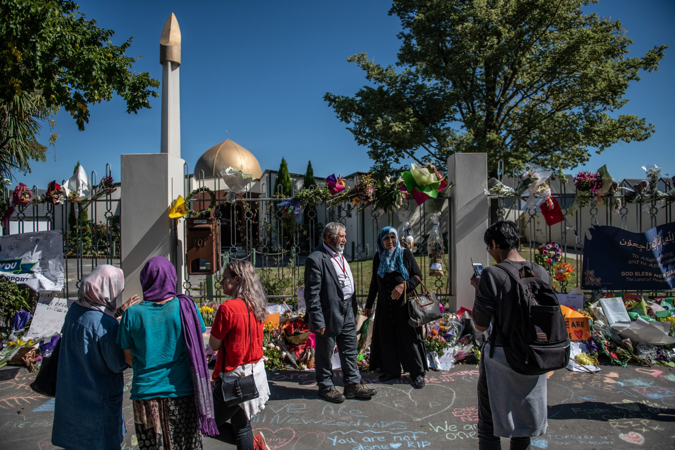 People pause next to flowers and tributes outside Al Noor mosque on March 24, 2019 in Christchurch, New Zealand. (Photo by Carl Court/Getty Images)