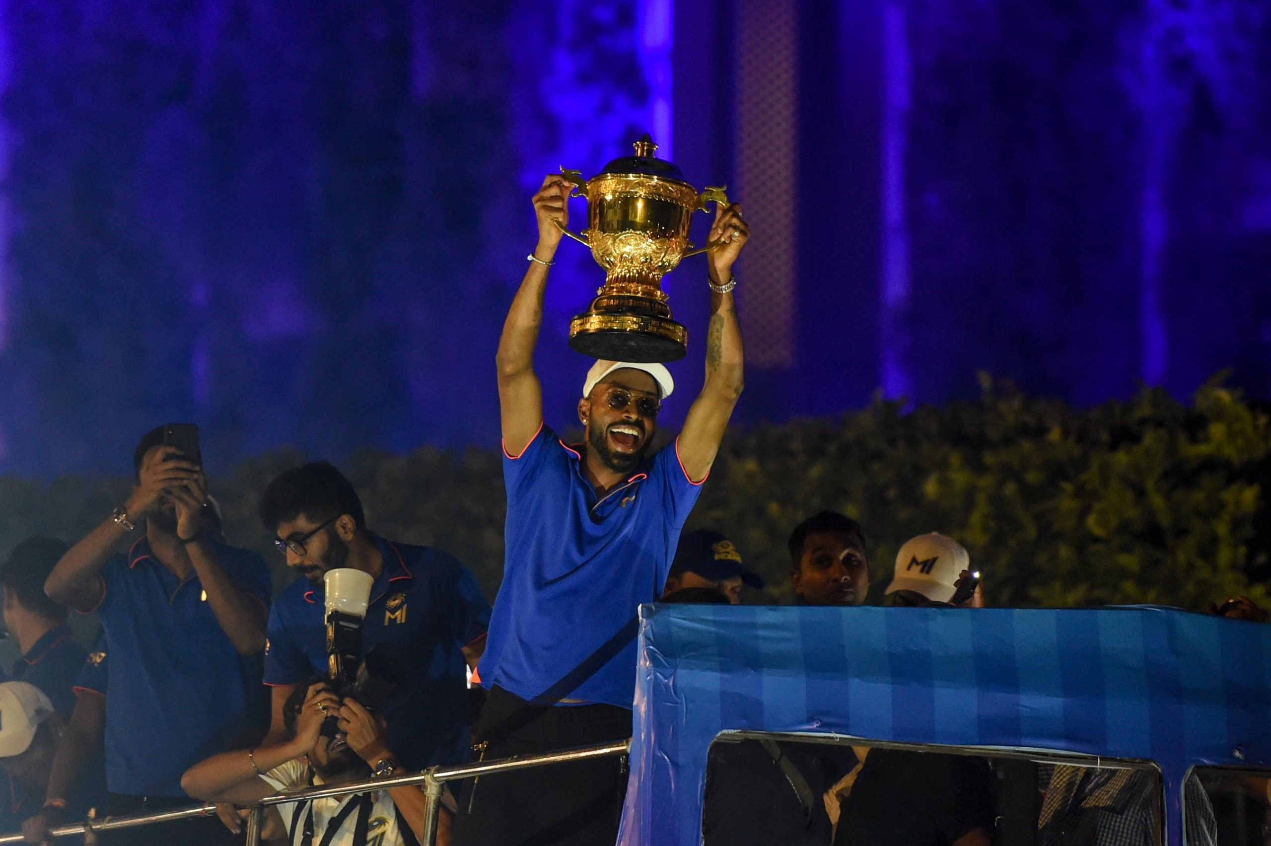 Mumbai Indians cricket player Hardik Pandya (C) holds the winning cup as the team travels in a open bus during a celebration procession after arriving in Mumbai on May 13, 2019. - Mumbai Indians team won the 2019 Indian Premier League (IPL) Twenty20 cricket tournament title. (Photo by PUNIT PARANJPE / AFP)        (Photo credit should read PUNIT PARANJPE/AFP via Getty Images)