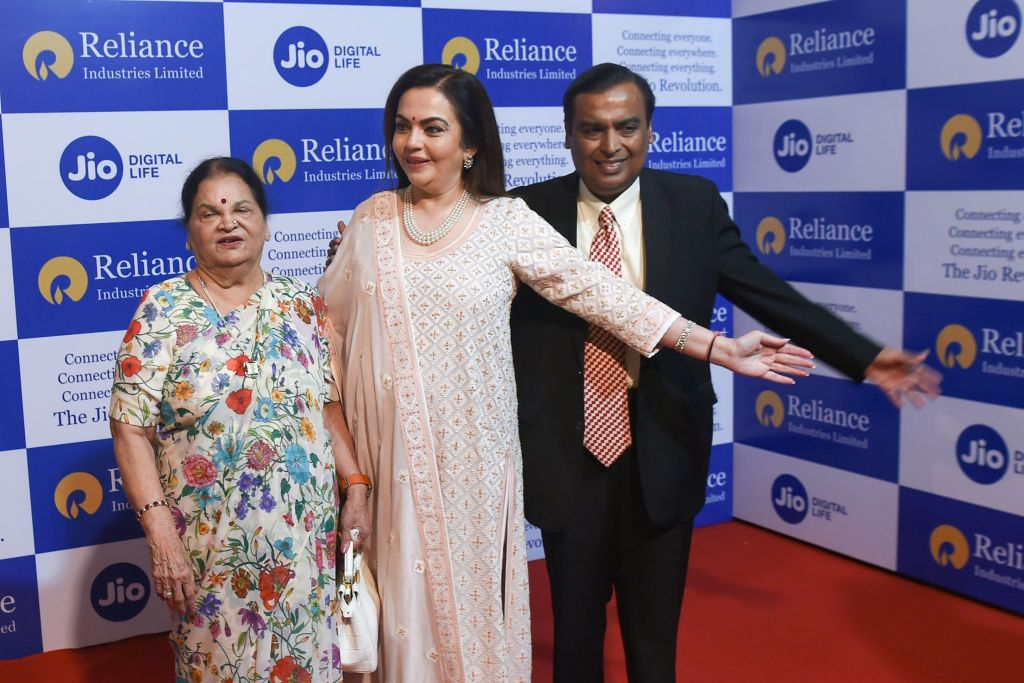 FILE PHOTO: India's richest man and oil-to-telecom conglomerate Reliance Industries chairman Mukesh Ambani (R) along with his wife Nita Ambani (C) and mother Kokilaben (L) welcome guests as they arrive for the company's 42nd AGM in Mumbai on August 12, 2019. (Photo credit should read INDRANIL MUKHERJEE/AFP via Getty Images)